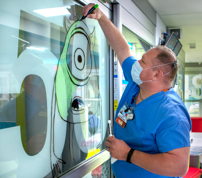 Stephen Supernavage, a registered nurse, draws on the patient room door in the COVID-19 unit in the Pediatric Emergency Department of Penn State Health Milton S. Hershey Medical Center on Tuesday, April 14, 2020.