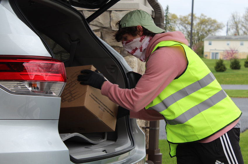 Aric Graham loads a free box of food into a car Friday, May 1, at Living Hope Church.