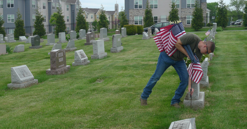 Robert Nezovich places a flag Thursday afternoon at the grave of a veteran buried in Middletown Cemetery.