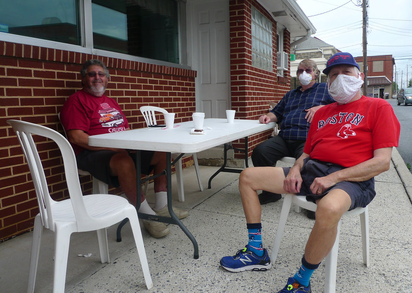 Malcolm Cohen (front right wearing baseball cap) of Linglestown, Perry Goldberg (rear right) of Harrisburg, and Alvin Rostolsky (left), also of Harrisburg, sit at a table for outdoor dining in front of Kuppy's in Middletown on Friday morning, June 5..
