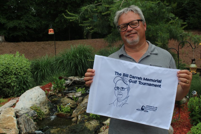Rex Rothrock holds a pin flag for the golf tournament he is putting on in memory of his longtime friend.