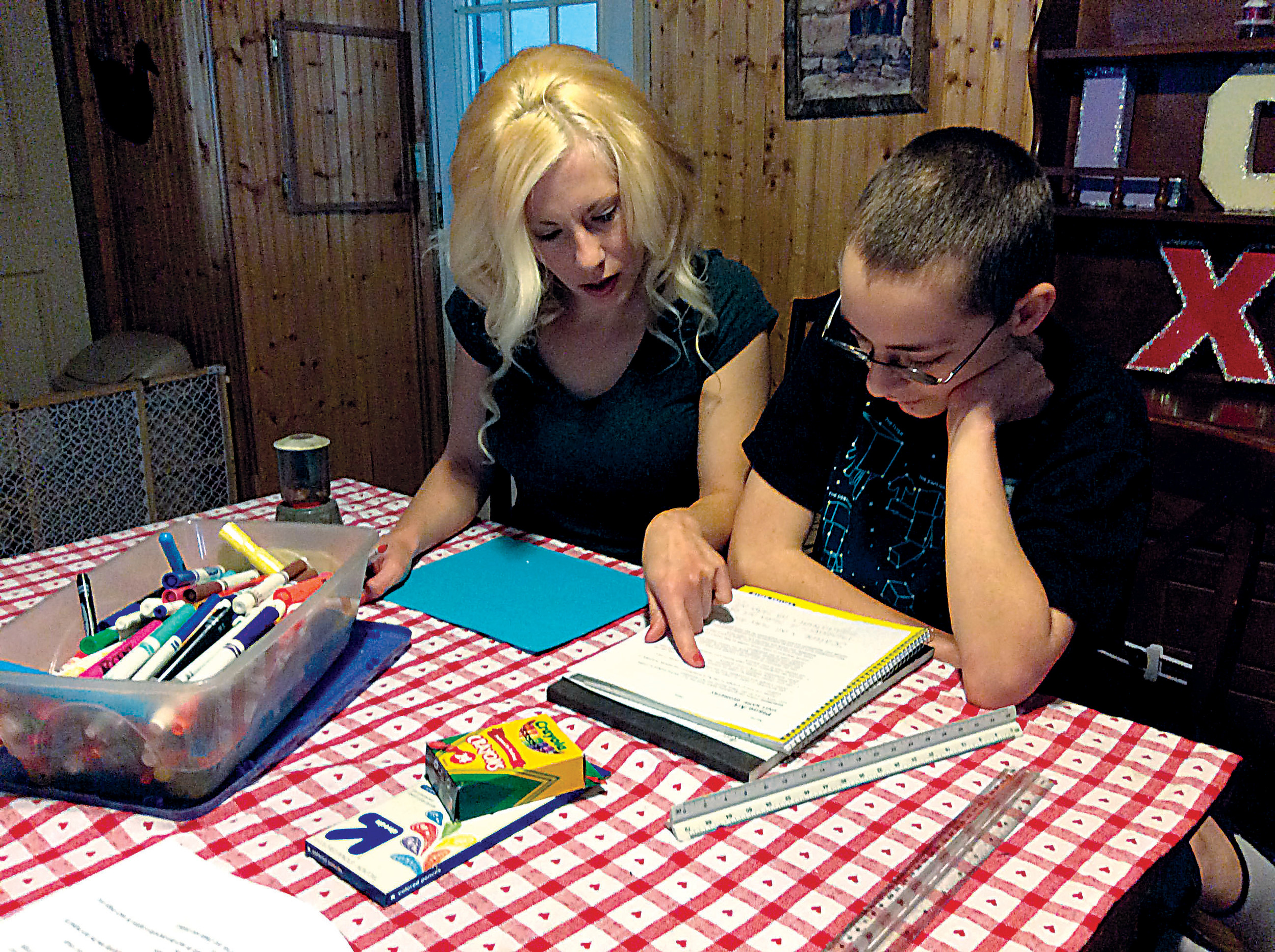 Nicole Robinson (left) gives a math lesson to her son Ethan (right) during home-schooling instruction at the kitchen table of their residence in Highspire.