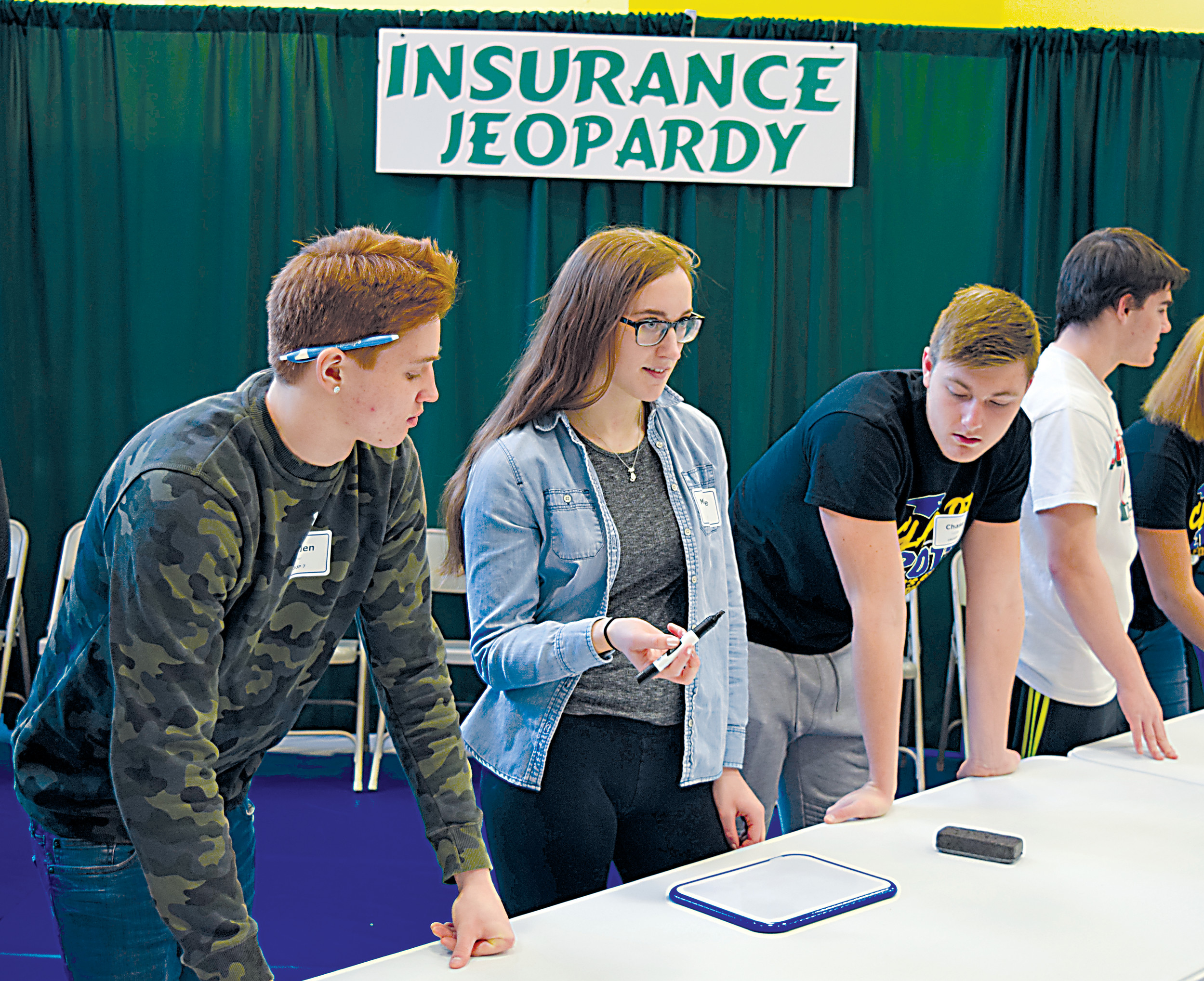 Braden Shetter, Michelle Shields and Chase Snavely play Insurance Jeopardy on Friday.