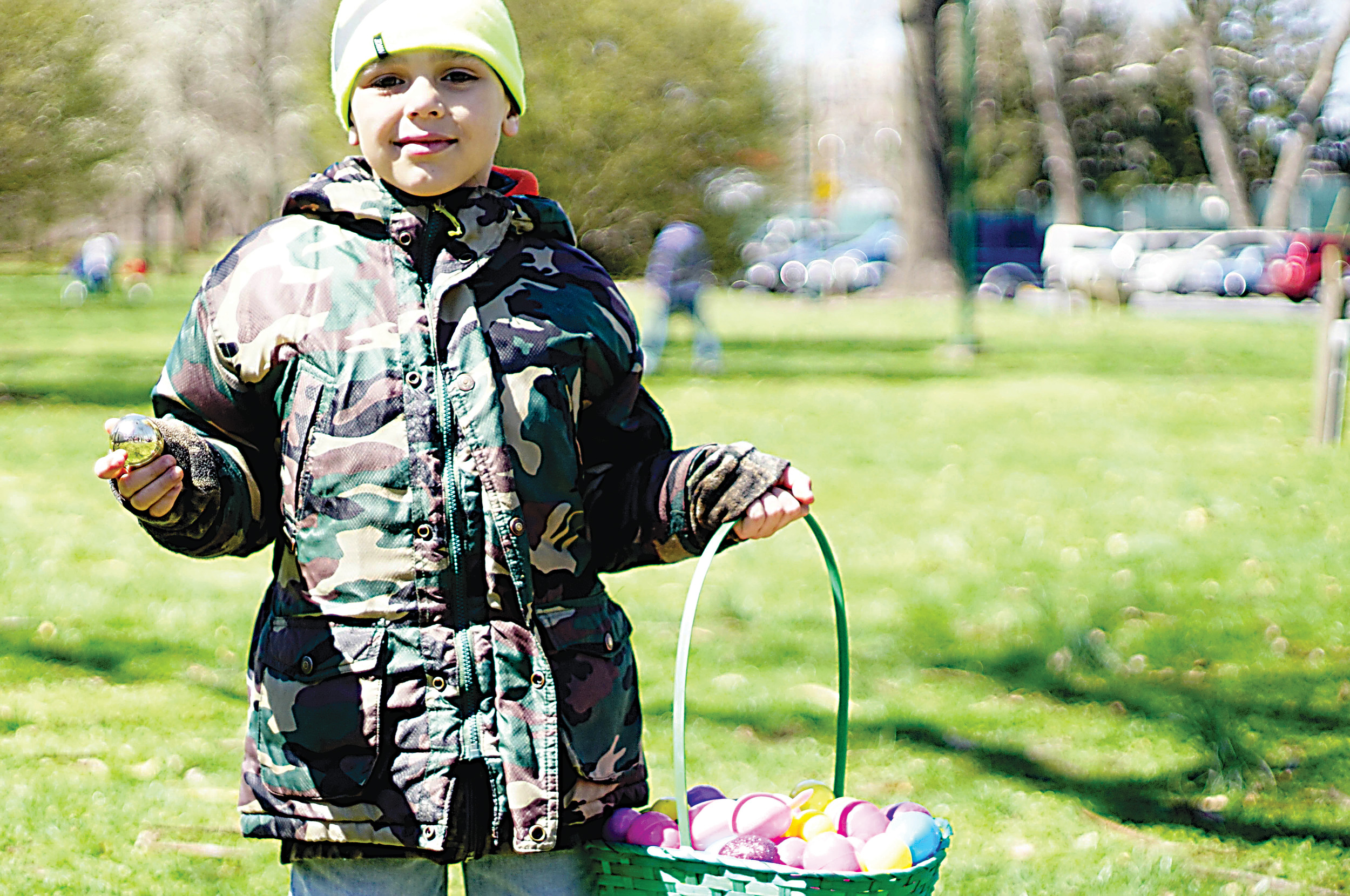 Josiah Chesney holds up one of five golden eggs that were among the 3,000 that were hidden during the Middletown Police Easter Egg Hunt