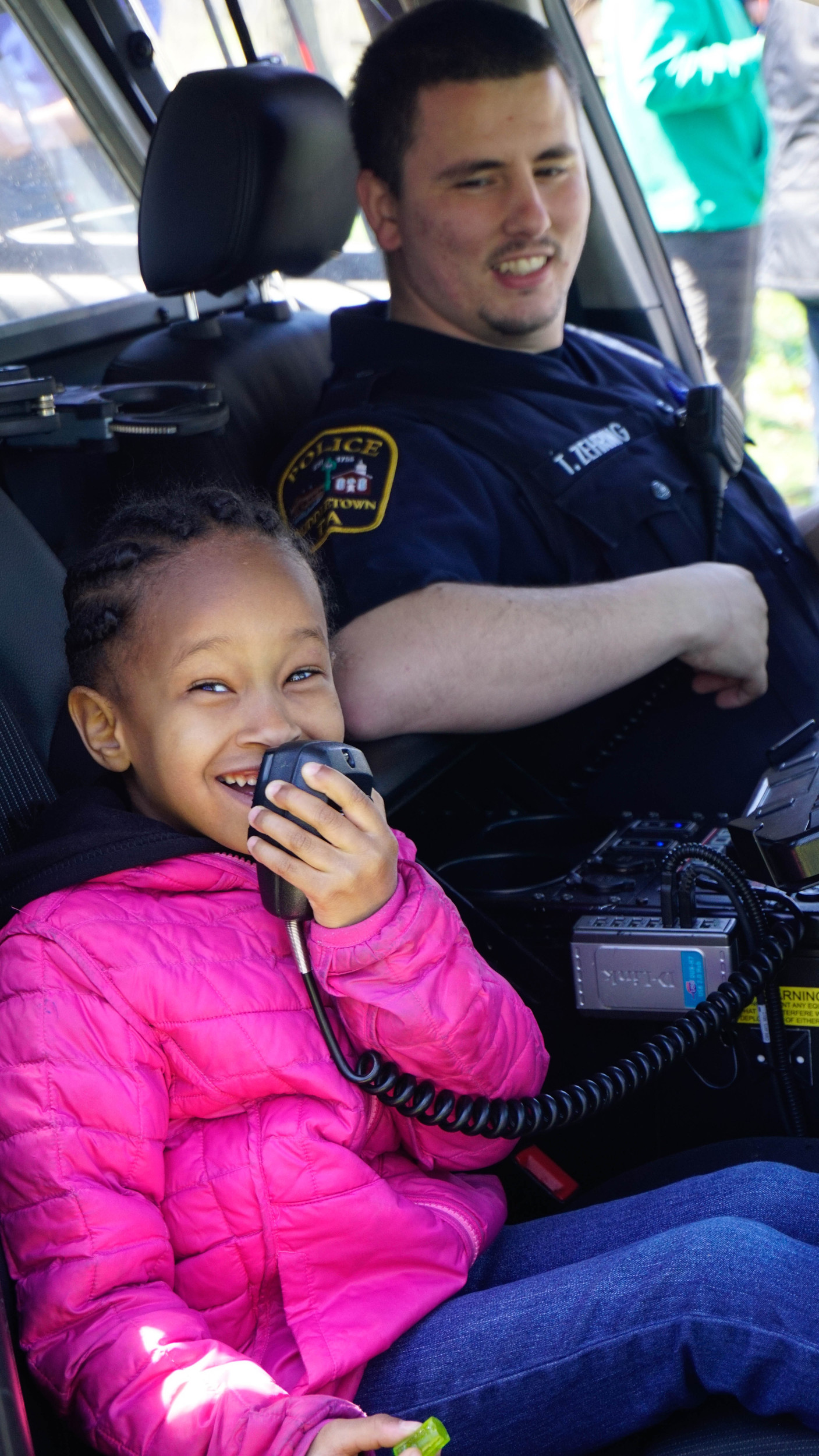 Samantha Mouchette, daughter of Interim Police Chief George Mouchette, uses the intercom in a police cruiser. Officer Tyler Zehring watches.