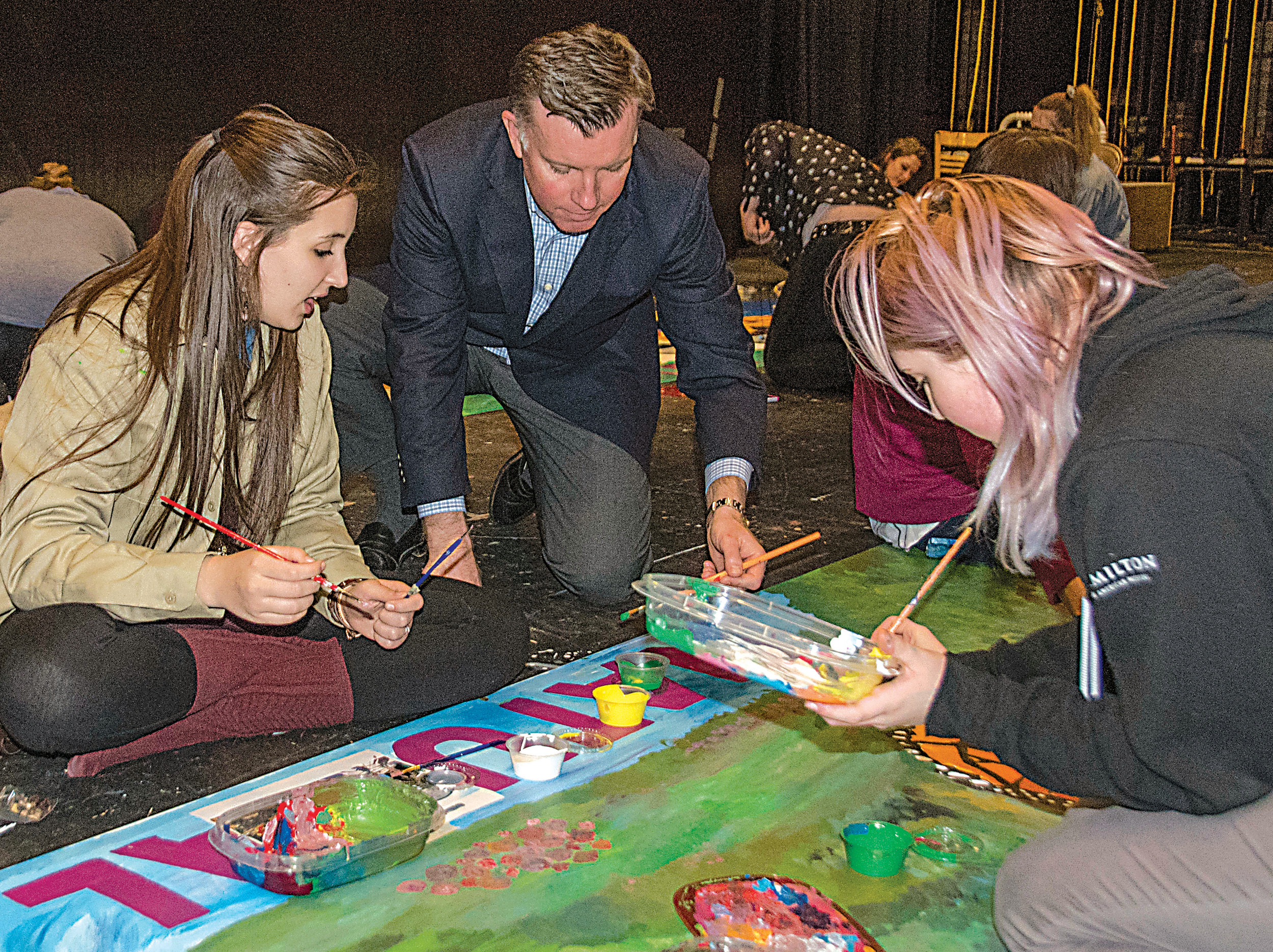 Lower Dauphin High School art students instruct Mark Compton, Pennsylvania Turnpike CEO, in painting techniques on March 30.