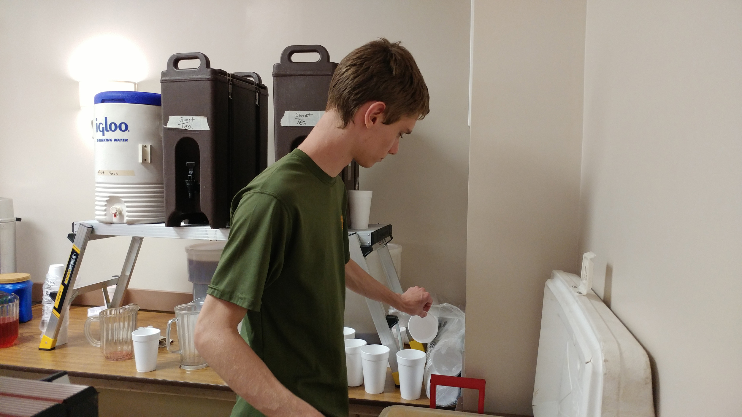 Boy Scout Brady Neithercoat of Troop 97 prepares ice and drinks for customers.