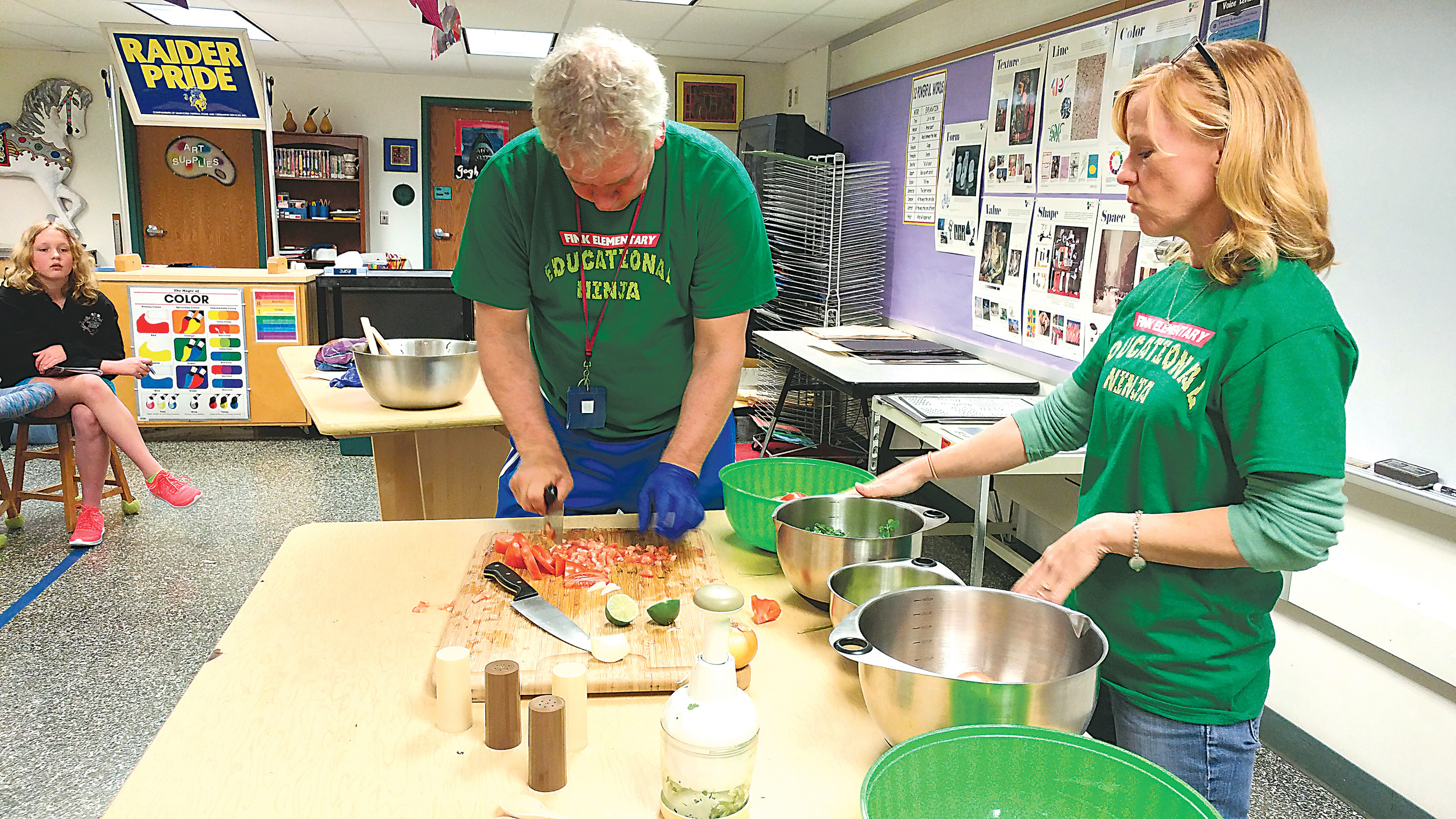 Michael Corney chops a tomato up during a salsa-making lesson during Cultural Day as Mindy Allison discusses the other ingredients needed for salsa.