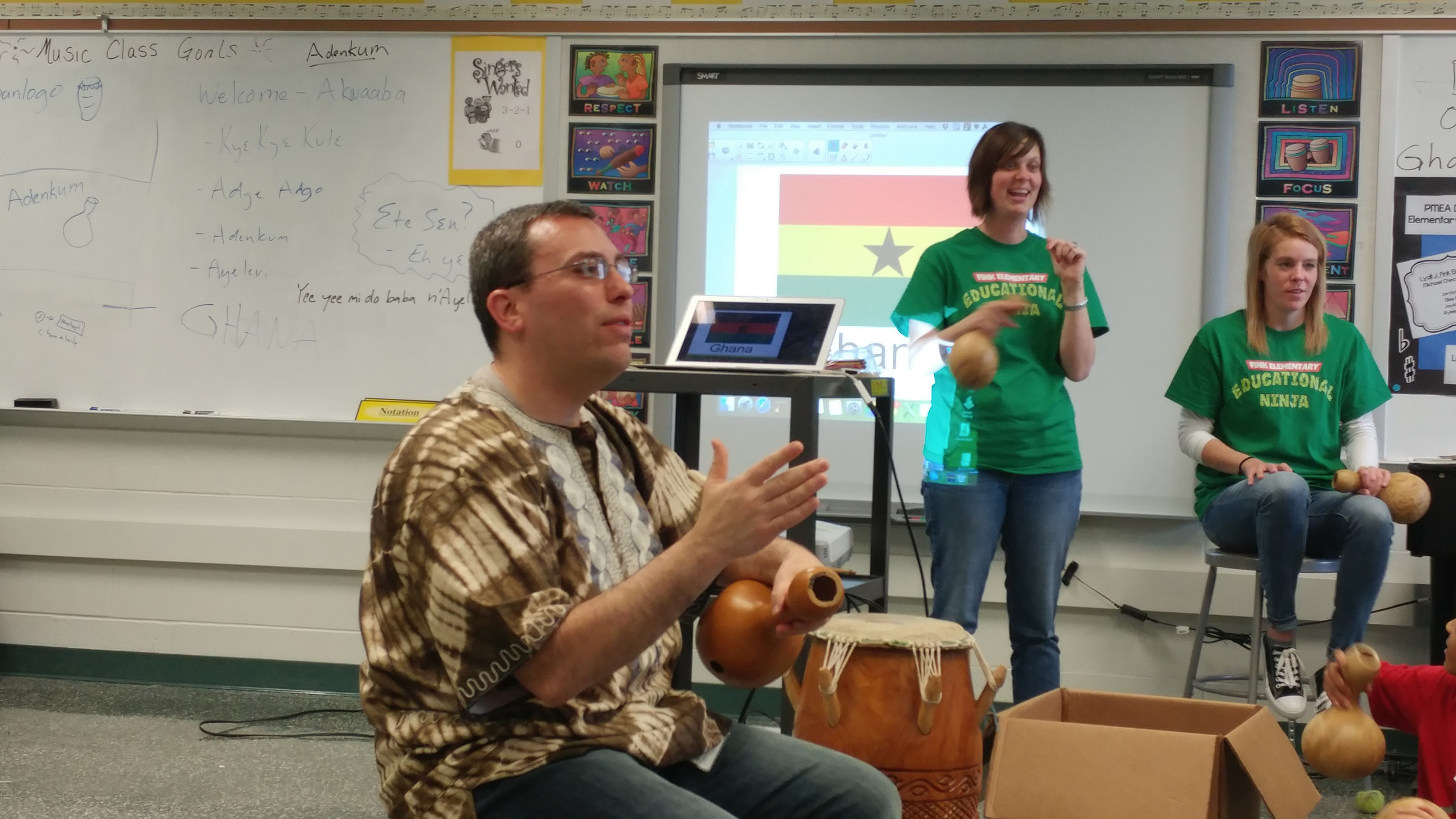 Michael Checco teaches students and teachers how to play an adenkum, a Ghanaian instrument made out of dried calabash gourds during Cultural Day at Fink.