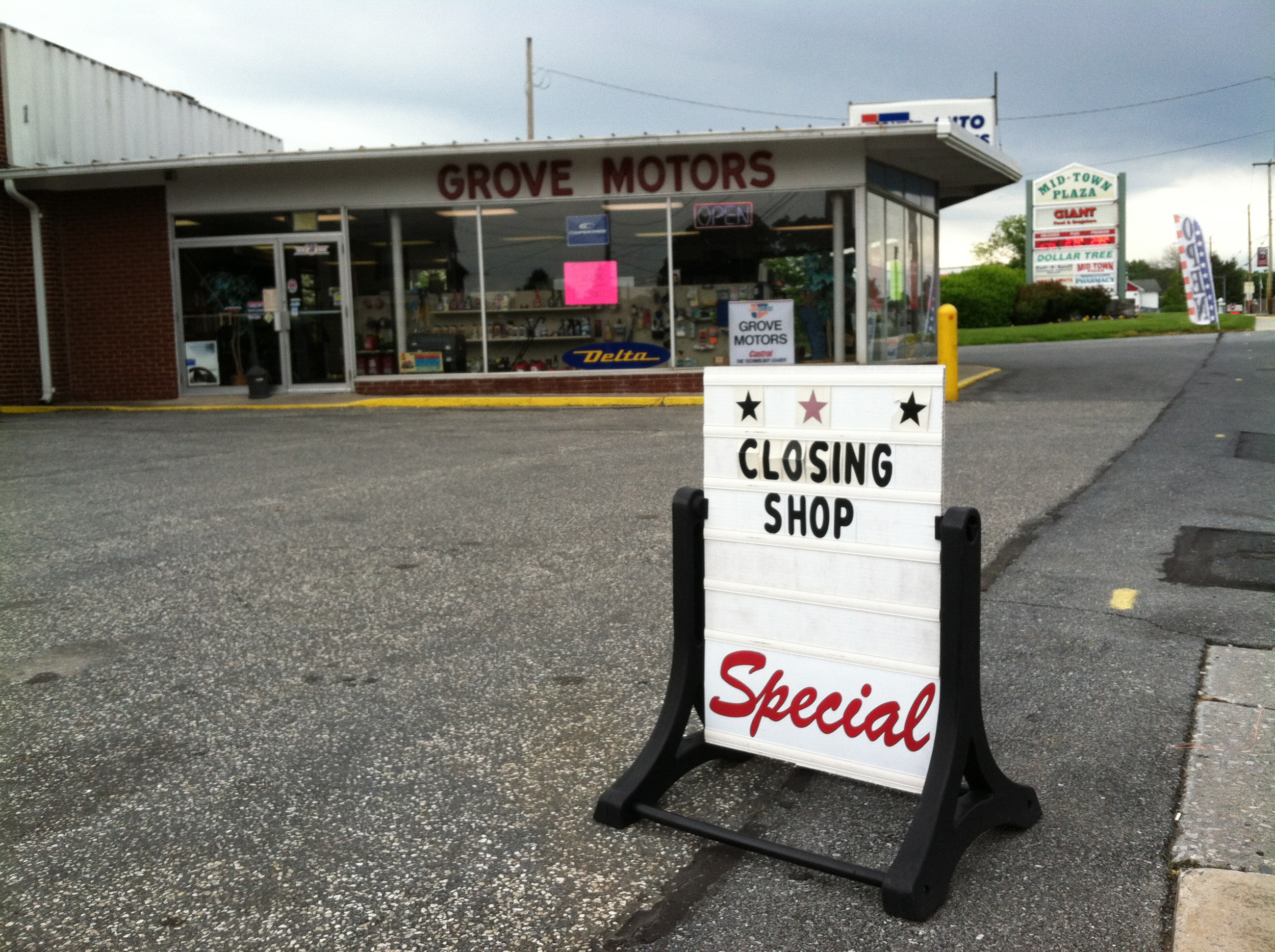 Sign posted near East Main Street alerts passing drivers that Grove Motors is closing.