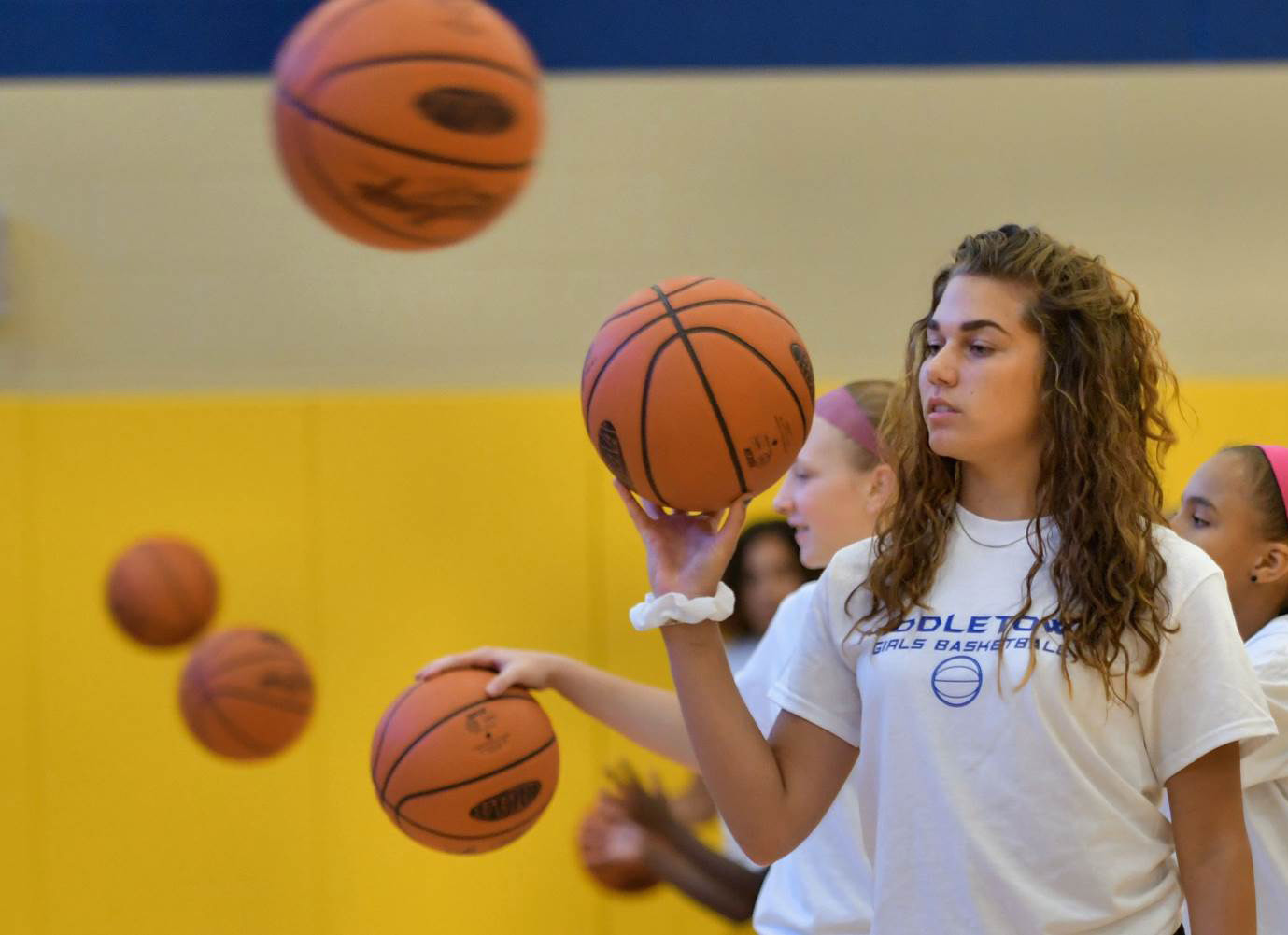 Basketballs surround Makaila Nester.