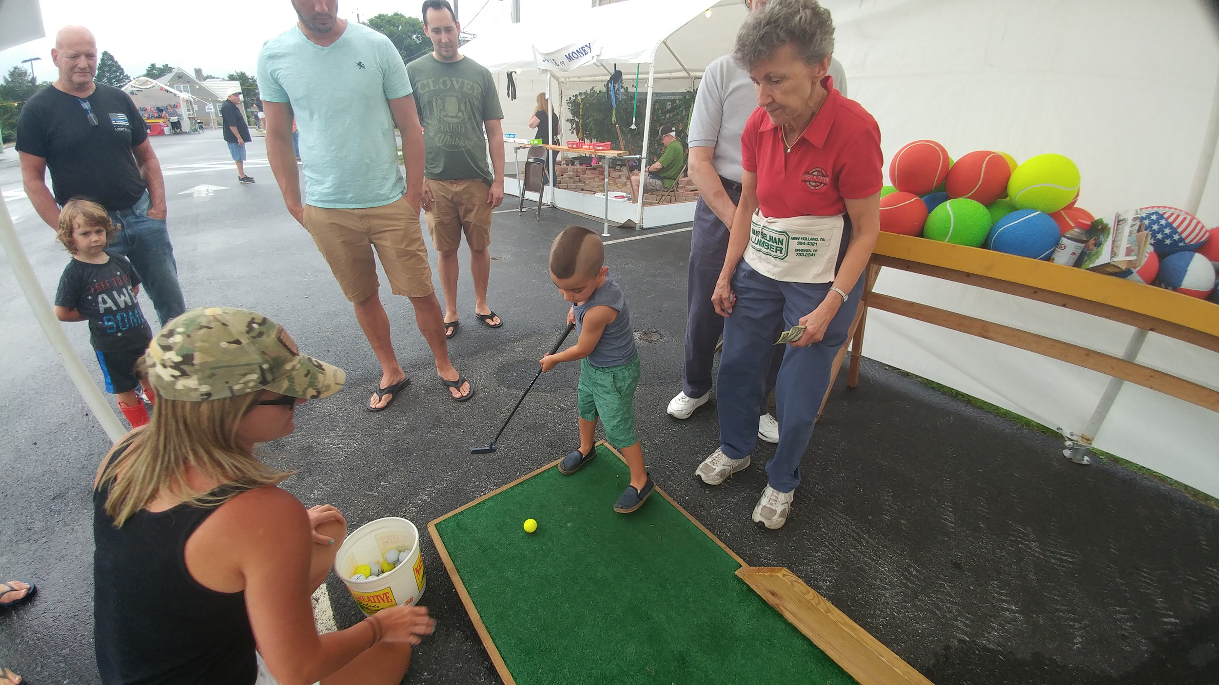 Jackson Cain, 3, tries to get a hole in one to win a prize during the festival Thursday night.