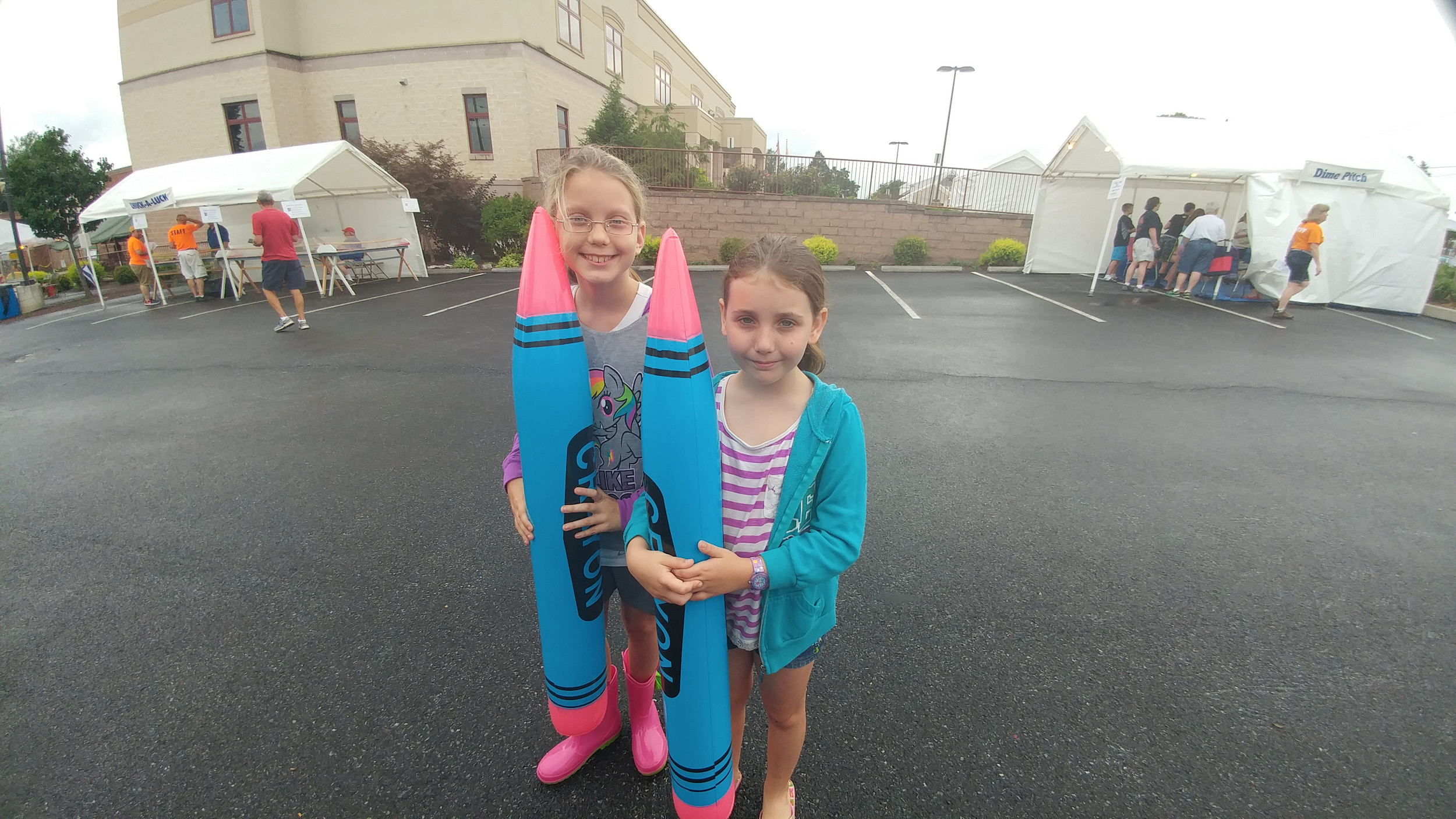 Emma Kieffer and her younger sister Phoebe show off their crayon balloons they won playing games at the Seven Sorrows Festival.