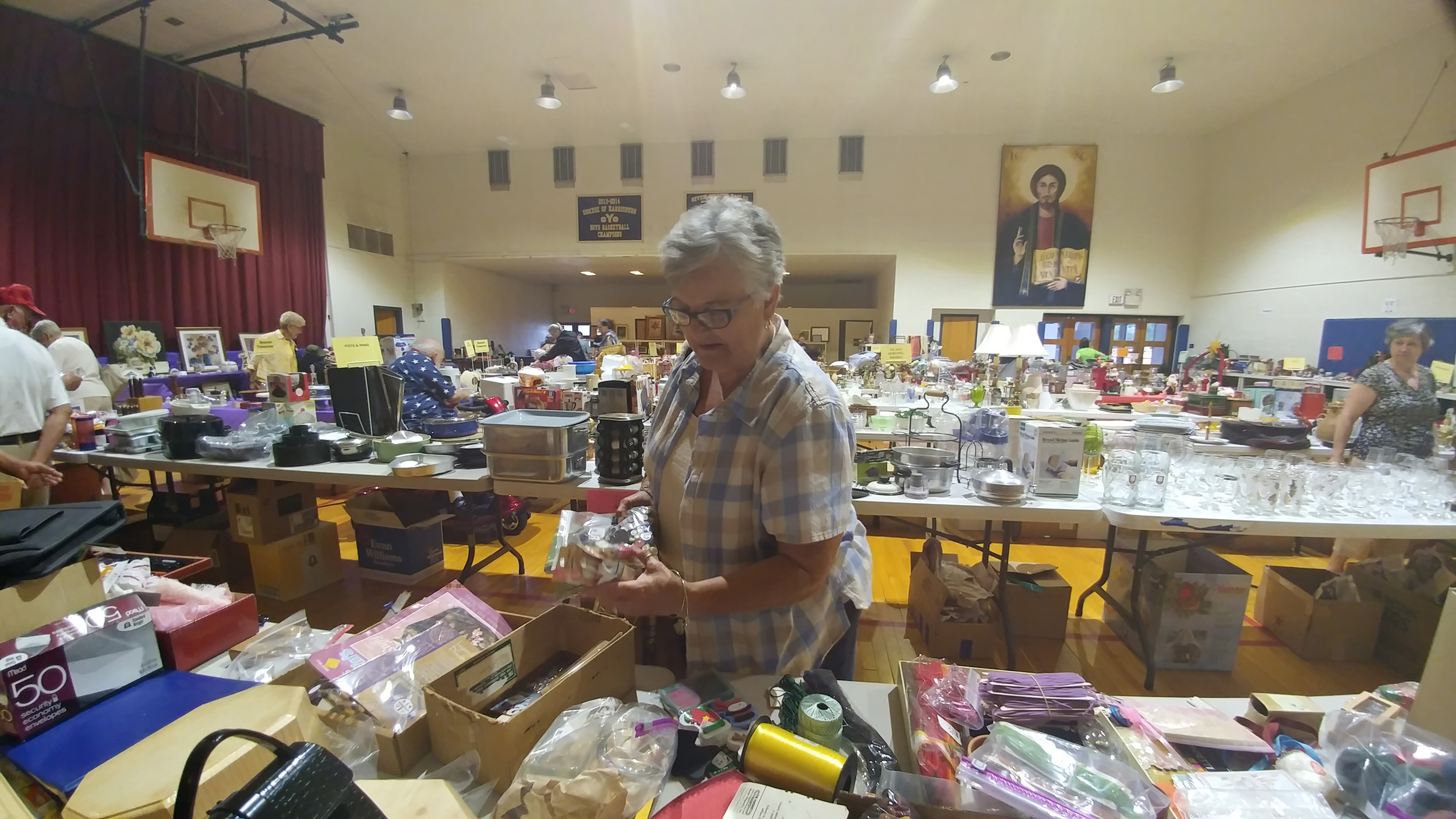 Donna Fallinger examines the items for sale at the Seven Sorrows Festival flea market held in the gym Thursday evening.