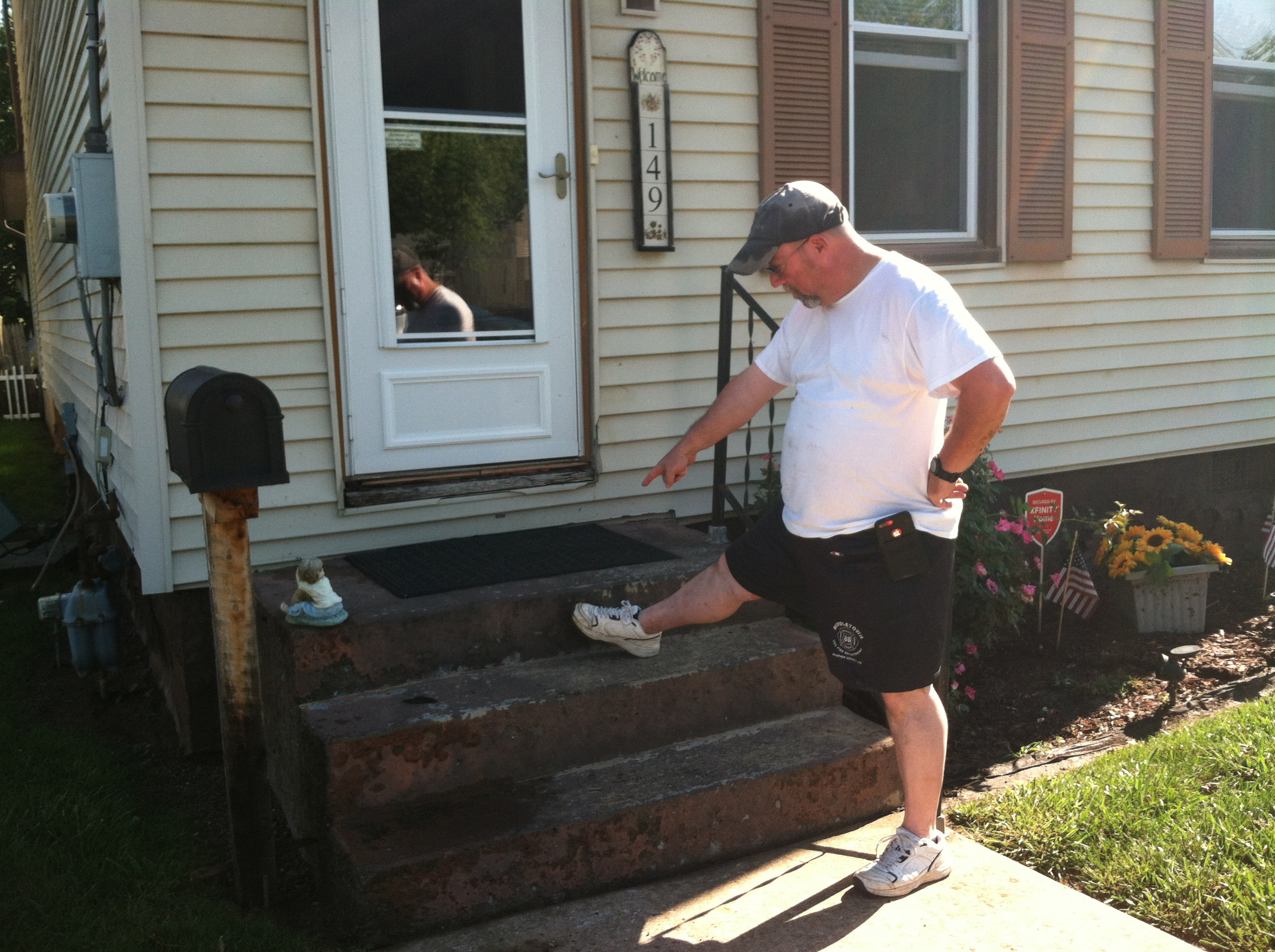 Ken Whitebread points to how high the water got on the steps in front of his house on Market Street in Middletown.