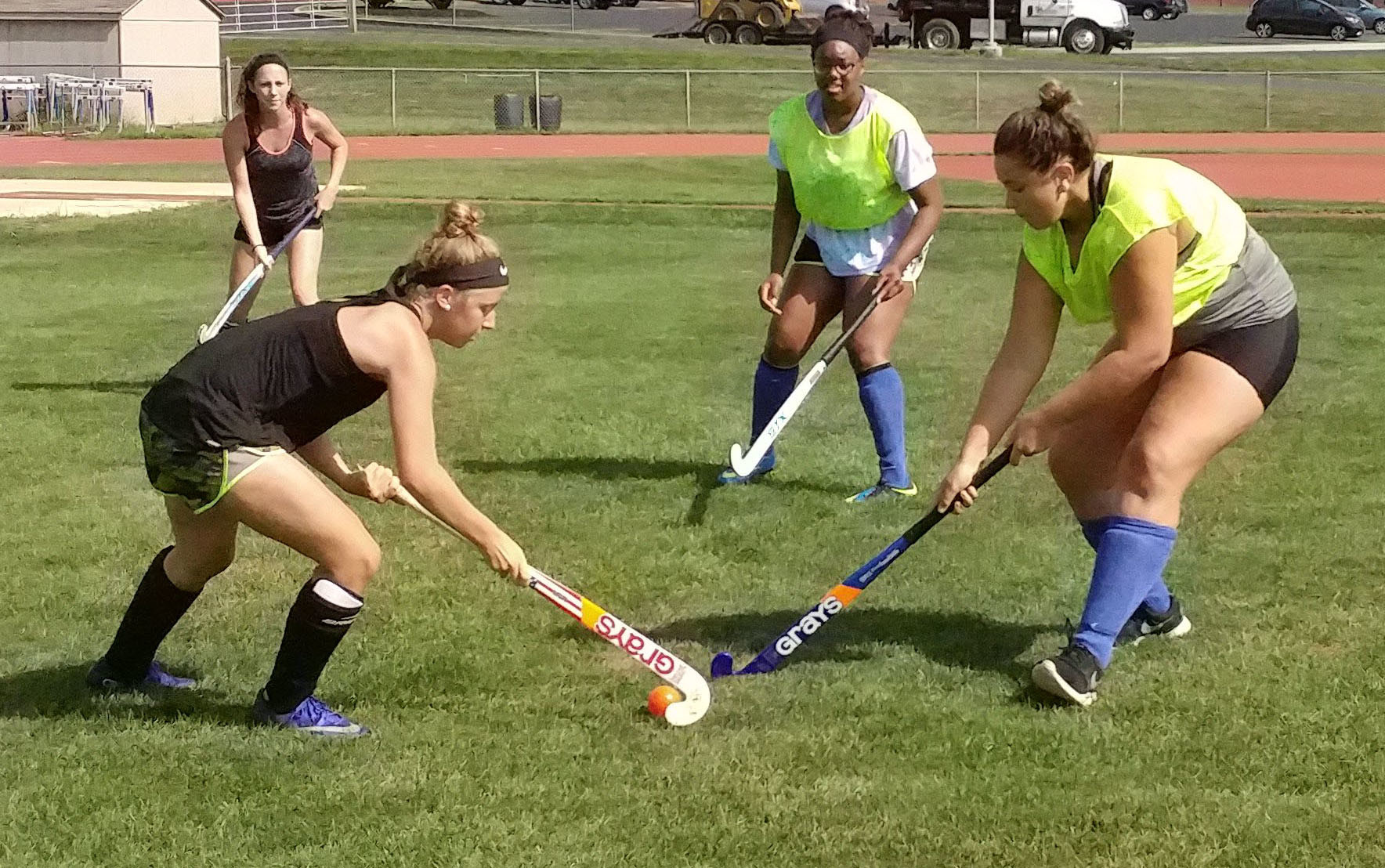 Paige Burger and Caroline Gill battle over the ball during field hockey practice on the morning of Aug. 25 while Kiera Guckavan and Deja Washington watch to see who gets the advantage.