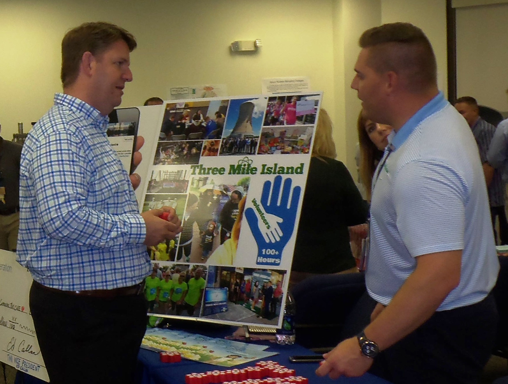 Company spokesman Dave Marcheskie, right, chats with a visitor during Three Mile Island Generating Station's Community Information Night on Sept. 7.
