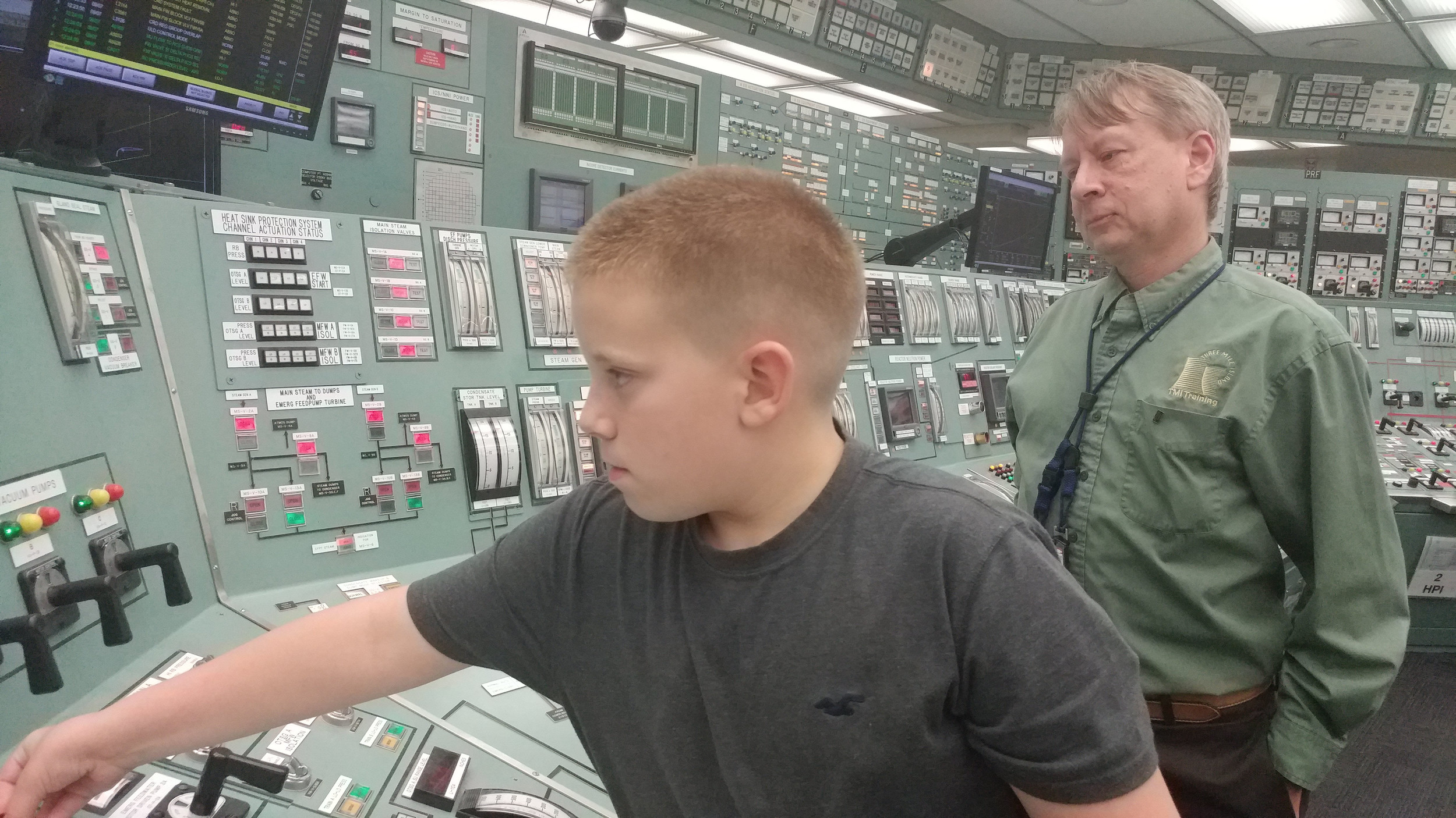 Greyson Albert, 9, demonstrates how to shut down the plant during a simulation at the TMI open house event on Thursday, Sept. 7 as John Tesmer watches.