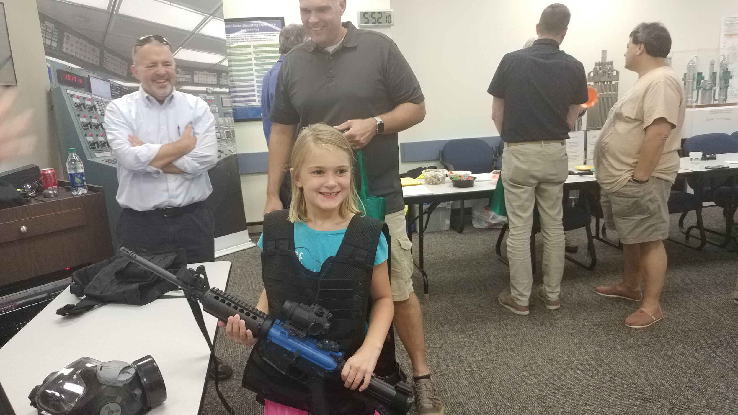 Abigail Reed, 7, tests out the bulletproof vest and mock gun potentially used by TMI employees in case of emergency at the open house event on Thursday, Sept. 7.