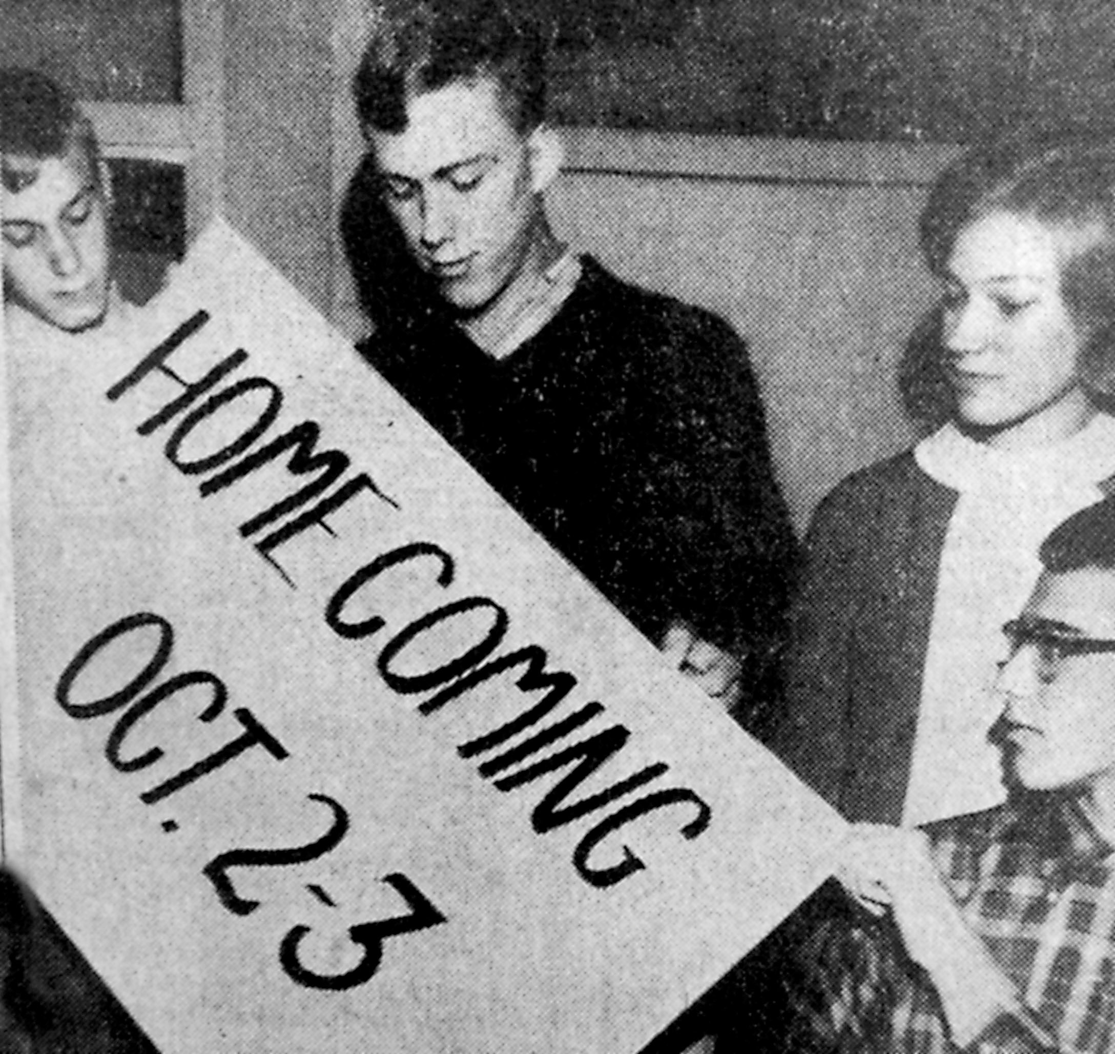 A banner is displayed by three members of the Middletown football squad and the captain of the cheerleaders. They encourage all graduates to attend the Milton Hershey game tomorrow, which begins at 7:30 after the crowning of a queen and a parade. There will be additional activities in the school Saturday, preceded by a banquet, The students are Richard Baker, seated; and from left, Jack Gochnaur, John Good and Nancy Houser.