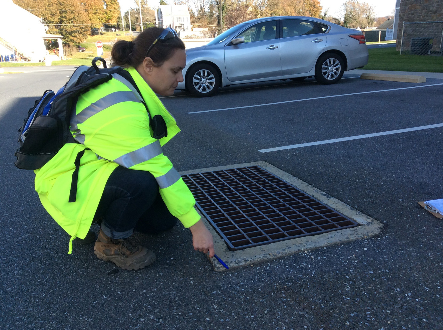 Penn State Harrisburg graduate student Sarah Ryan shows how stormwater is not flowing into a drain as it should, because the drain is sitting too high above the macadam.