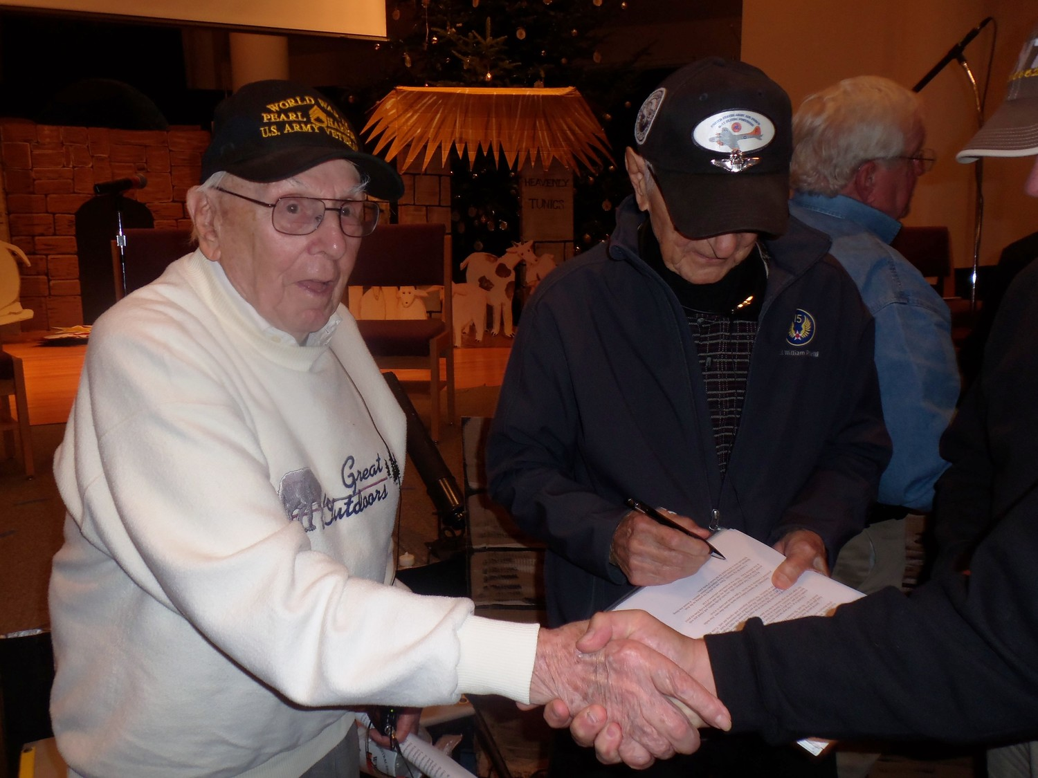 "Pearl Harbor survivors Richard ""Dick"" Schimmel, left, and William Bonelli, shake hands and sign books for audience members after they spoke at the Central Pennsylvania WWII Roundtable at Grace United Methodist Church, Hummelstown, on Dec. 7, the 76th anniversary of the attack."
