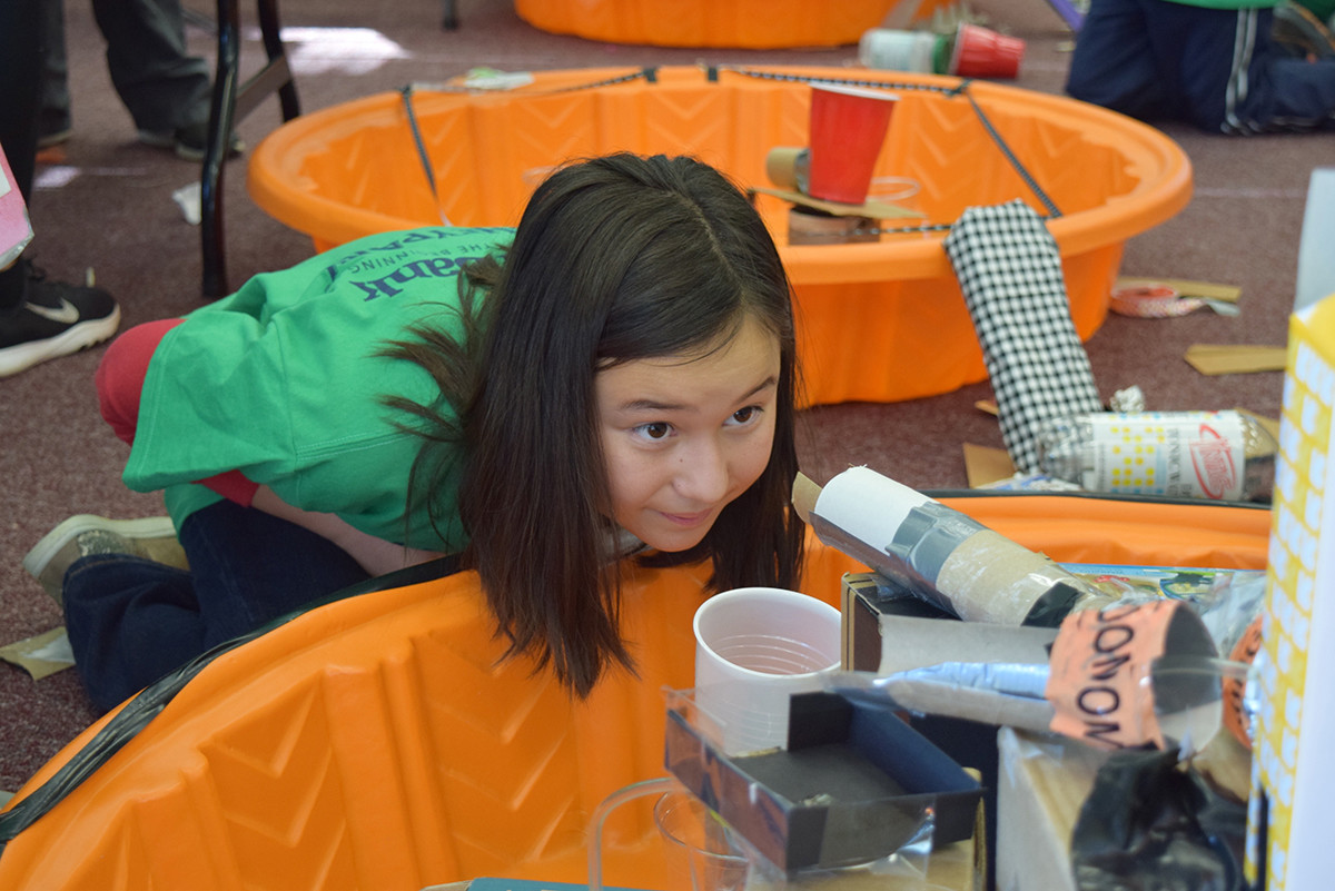 Lower Dauphin School District 5th grader Chloe Chang aims for a closer look inside of the project her team is working on.