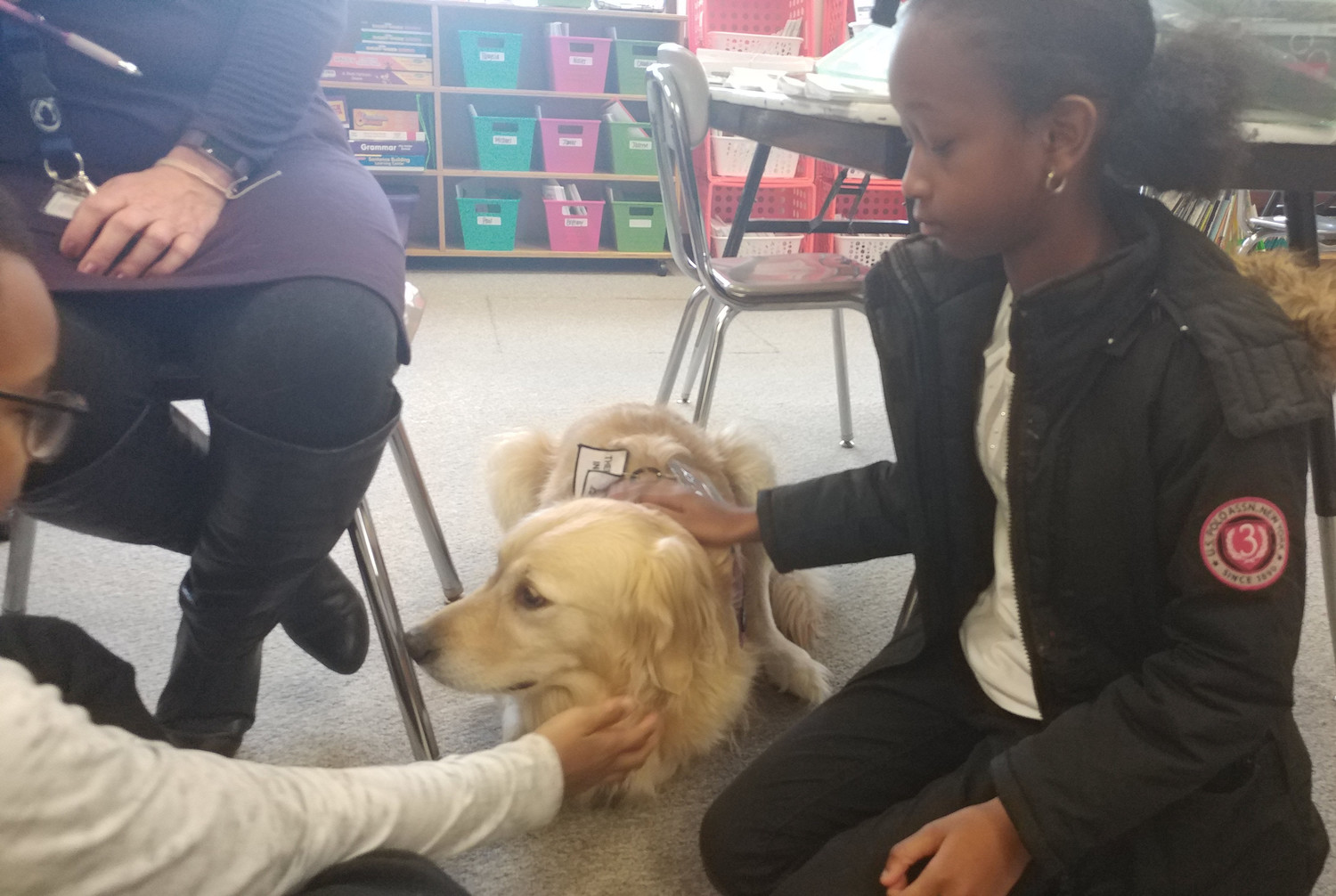 Talaysia Roy pets Mia while Nisier Franklin gets in on the petting as well during class on Tuesday, Nov. 21 at Kunkel Elementary School.