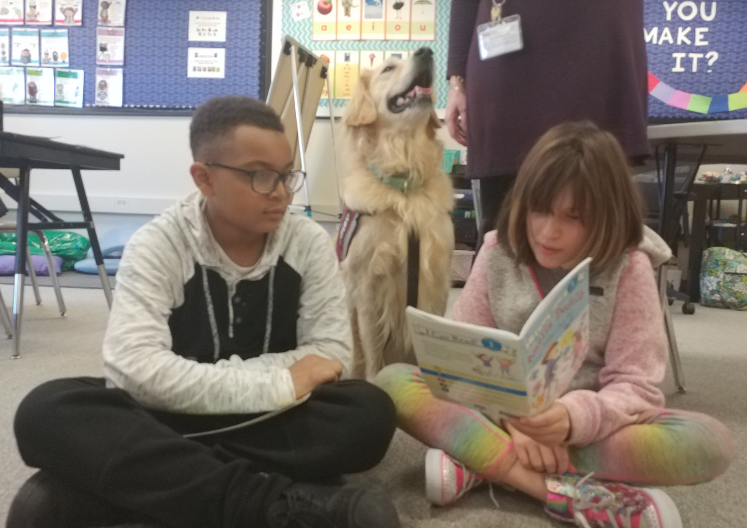Students Brittany Garner and Nisier Franklin participate in a reading activity at Kunkel Elementary as Mia the district's therapy dog listens to Garner read.