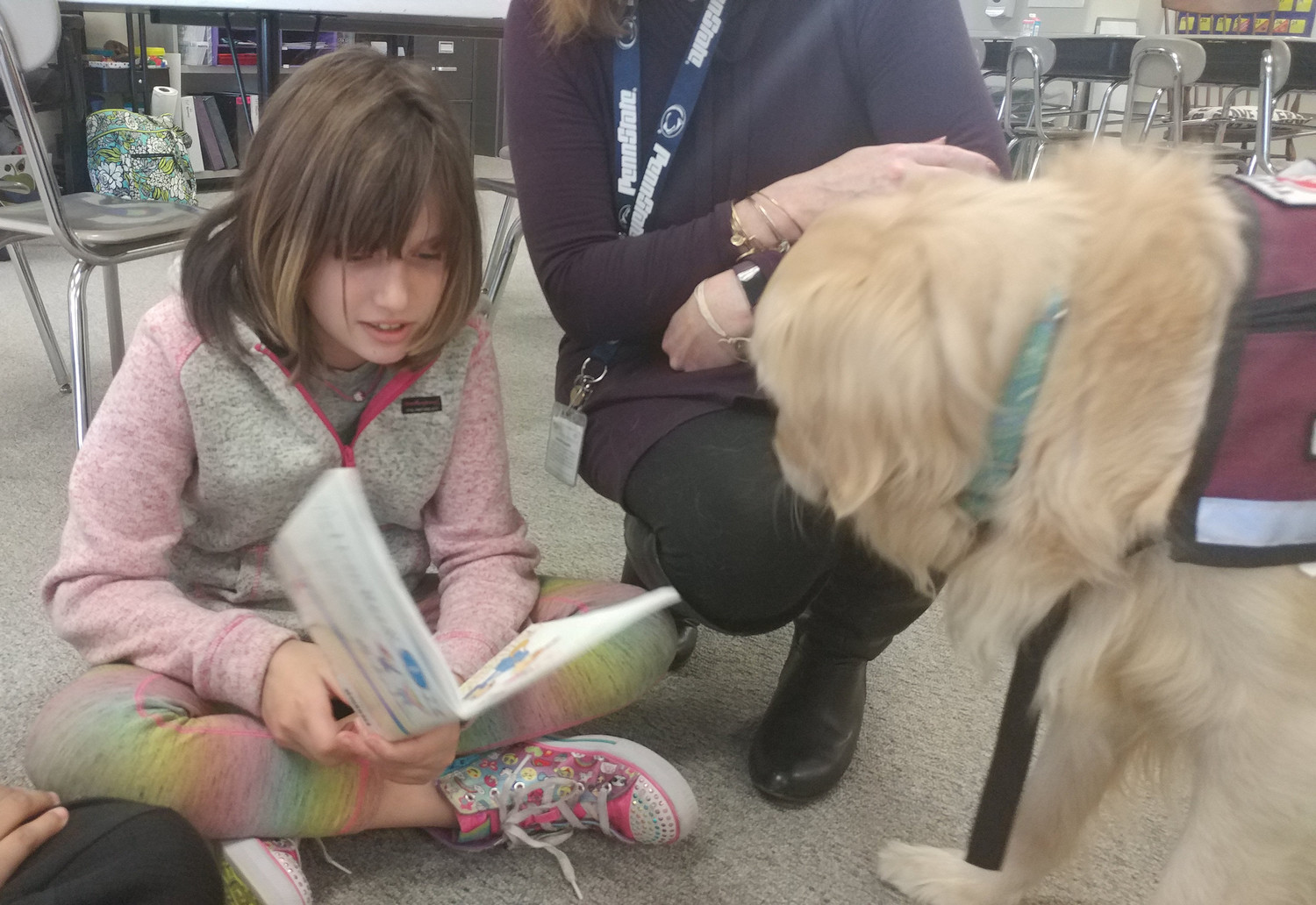 Mia listens as Brittany Garner reads a story. It's been said and proven that dogs make good reading partners since they won't criticize or pressure students when they pronounce a word incorrectly.