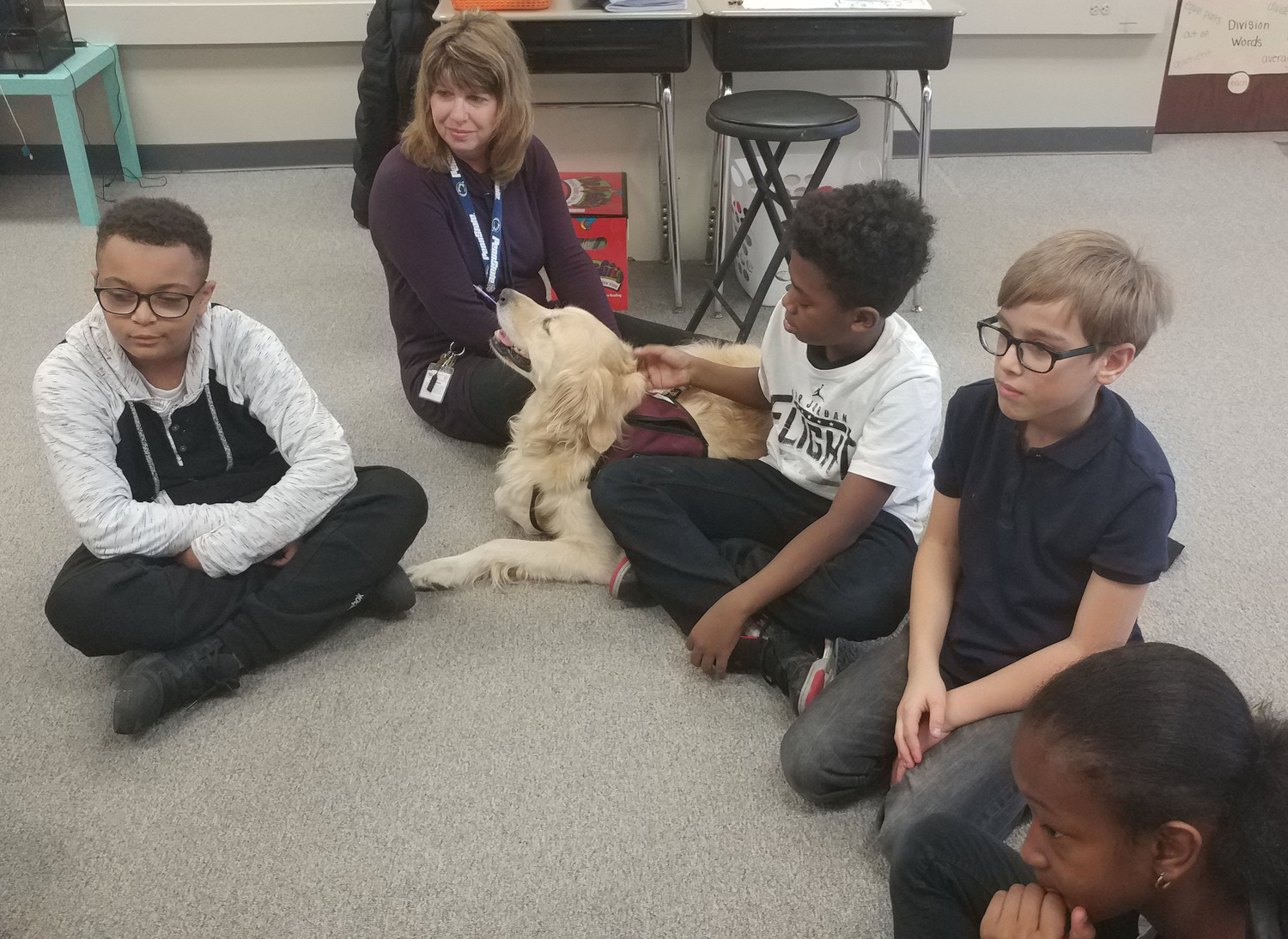 Jamar Neal pets Mia while classmates Nisier Franklin, Paul Reiseg, and Talaysia Roy listen to a story on Nov. 22 at Kunkel Elementary School.