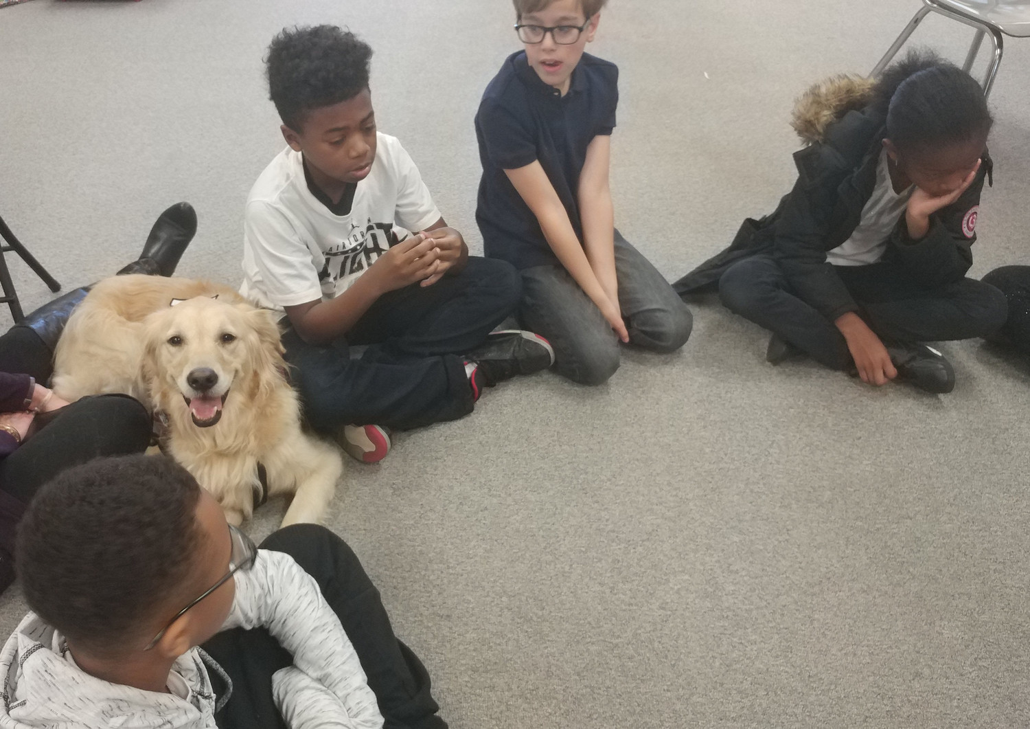 Nisier Franklin, Jamar Neal, Paul Reiseg, and Talaysia Roy listen to a story on Tuesday, Nov. 22 while enjoying the company of Mia, the Middletown Area School District's therapy dog.