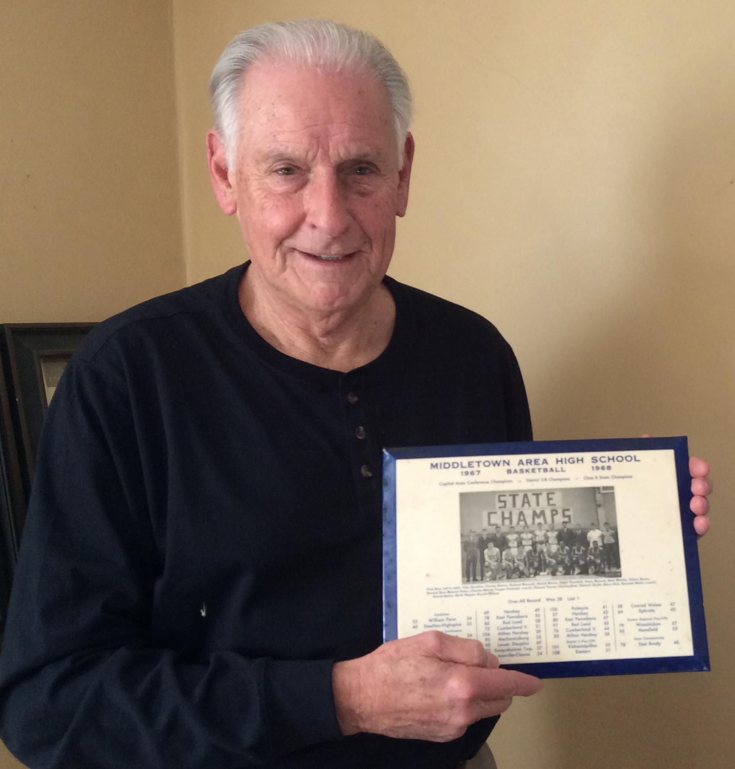 Casper Voithofer shows the team picture from the 1968 state championship Middletown varsity boys basketball season that he keeps in a room at his house in Lower Swatara Township.
