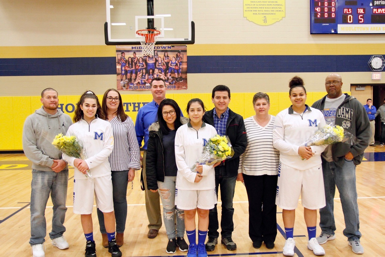 Middletown girls basketball coach Ron Stetler, in blue shirt, says goodbye to seniors Makaila Nester (with Jeff and Carrie Nester), Erika Gonzalez (with Patricia and Pablo Gonzalez) and Morgan Noon (with Kim and BJ Noon) on Jan. 22, during Senior Night festivities. They lost to Milton Hershey, 50-43.