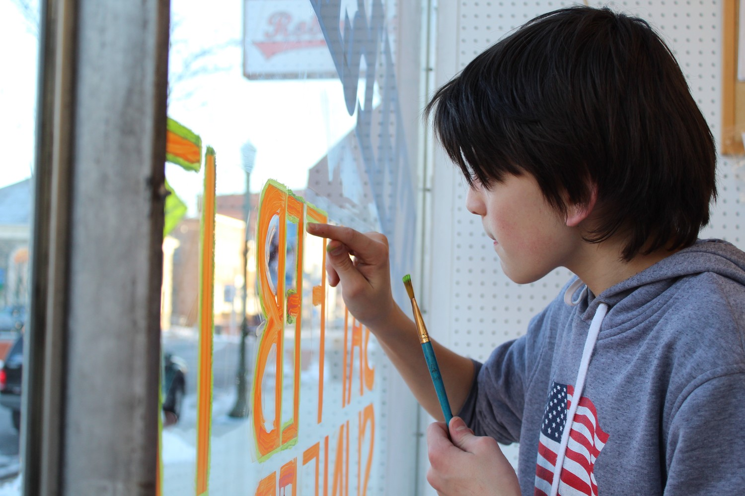 Tyler Ditzler paints the front window of the thrift shop.