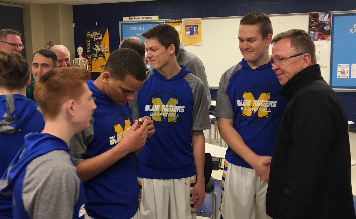 Middletown basketball players Jerrod Myers, Antonio Gamble, David Alcock and Mitch Lee examine the NBA championship ring of Dave Twardzik, right, before Friday's Blue Raiders game vs. West Perry. Twardzik, who won a title as a member of the 1977 Portland Trailblazers, was a member of the 1968 MAHS state championship basketball team that was honored at halftime.