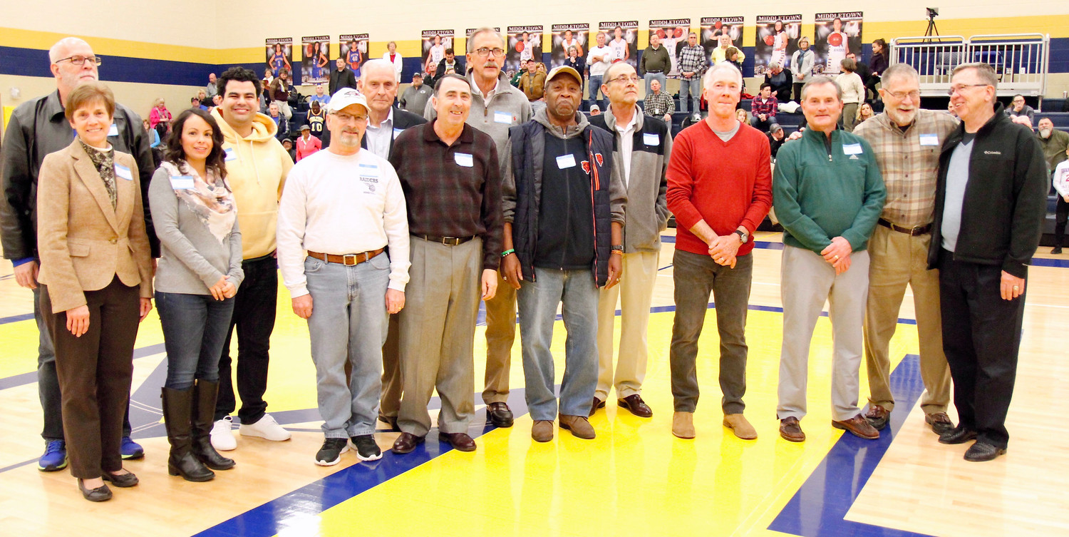 The 1968 state champion Middletown Blue Raiders basketball team was honored at halftime of Friday's home game vs. West Perry. From left are Pat Ethridge and Gary Tennis (family of the late Ed Tennis), Janelle Sostar and Julian Hannah (family of Owen Hannah), trainer Sam Turns, coach Casper Voithofer, trainer Jerry Butler, and players Ed Chubb, Brett Whittle, Barry Ulsh, Charlie Bowen, Dick Barnoski, Chip Etter and Dave Twardzik.