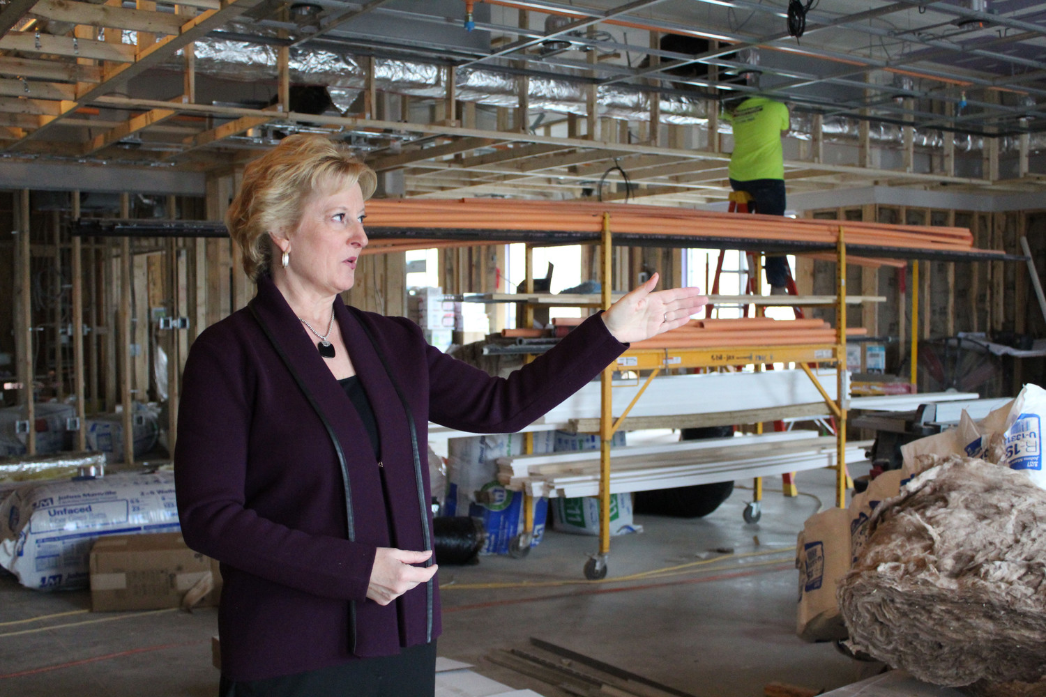 Janice Murray, director of operations of Restin Hospitality LLC, the company that owns the Comfort Inn & Suites, points out the future lobby fireplace while work continues behind her during a tour Feb. 12.