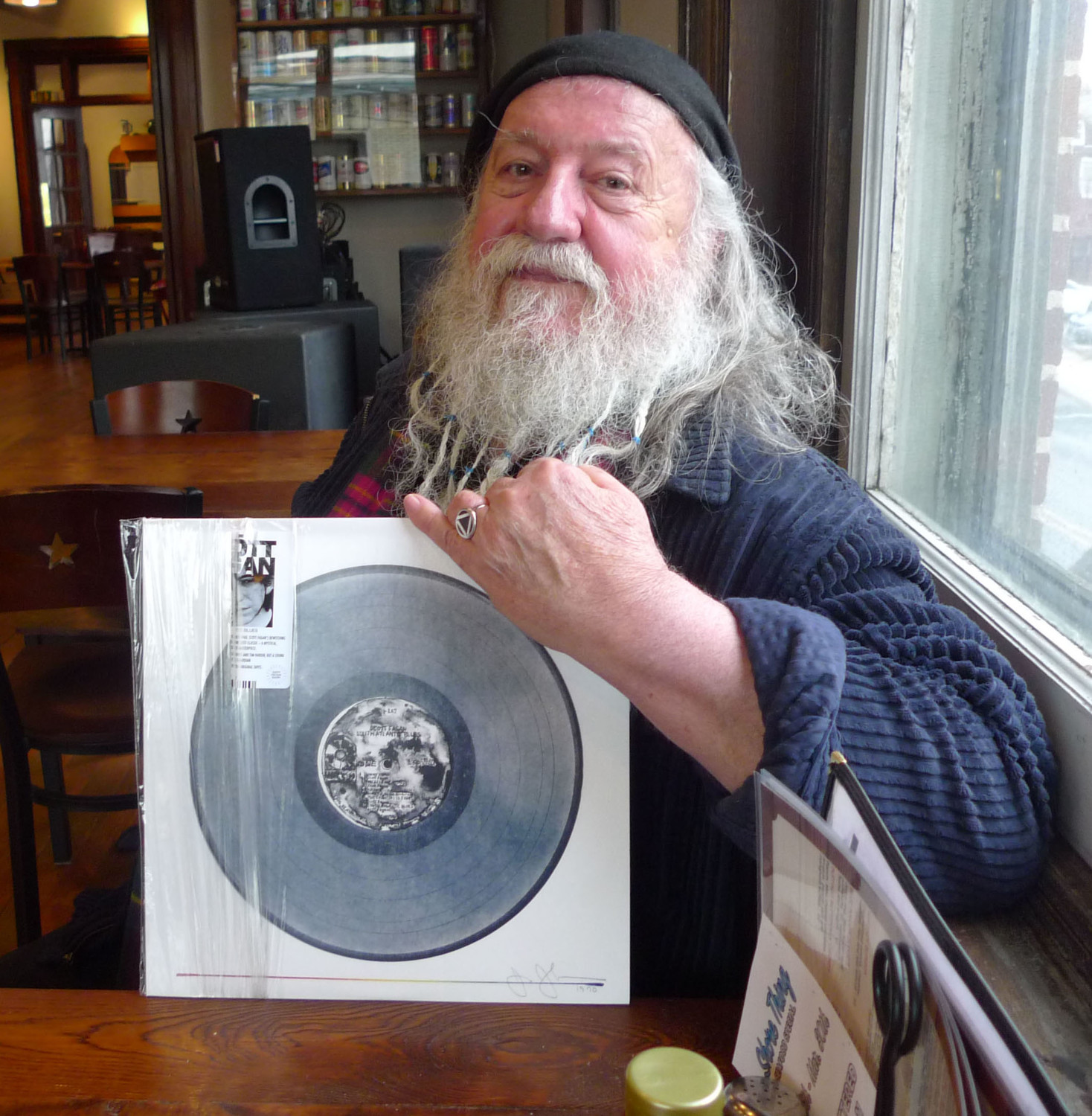 "Scott Fagan holds a signed copy of a lithograph created by famed artist Jasper Johns inspired by his album ""South Atlantic Blues."" Fagan is sitting on the second floor of the Tattered Flag Brewery and Still Works, where he will perform March 16."
