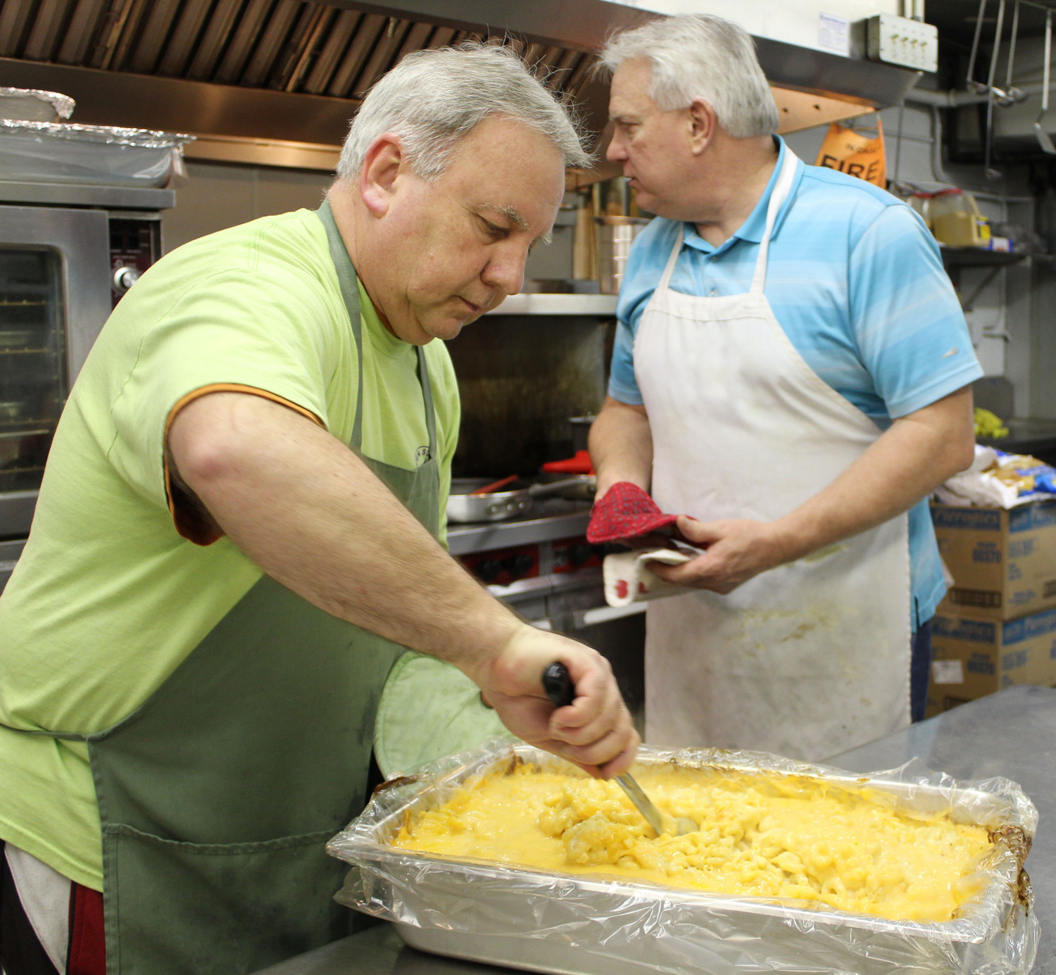 Lou Tschachler stirs macaroni and cheese at Seven Sorrows.