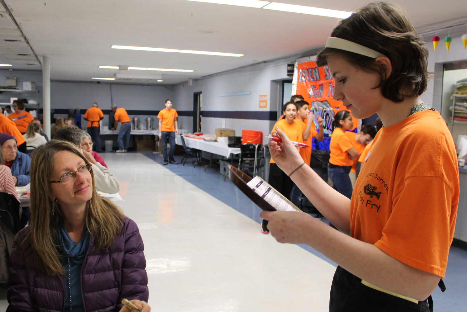 Hannah Arnold  takes Marsha Elmer's drinkorder during Seven Sorrows' fish fry.