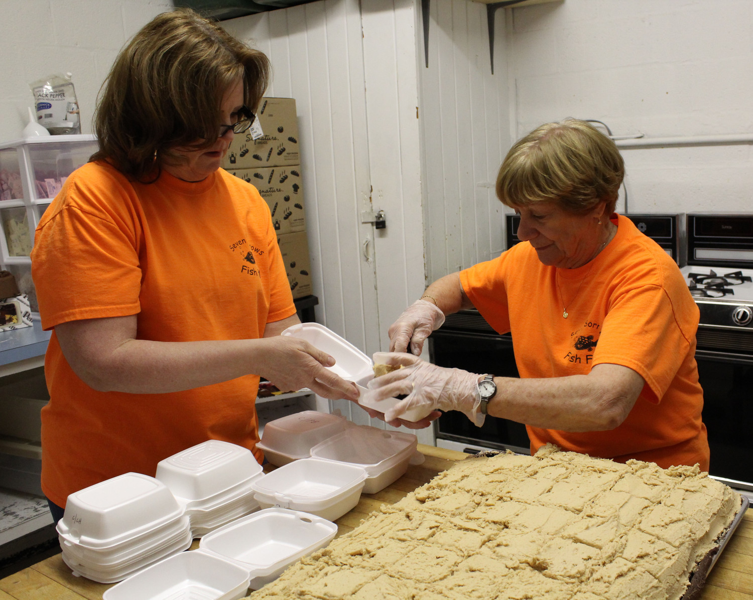 Gail Pakosky and Evelyn Shields pack cake into styrofoam boxes for to-go orders.