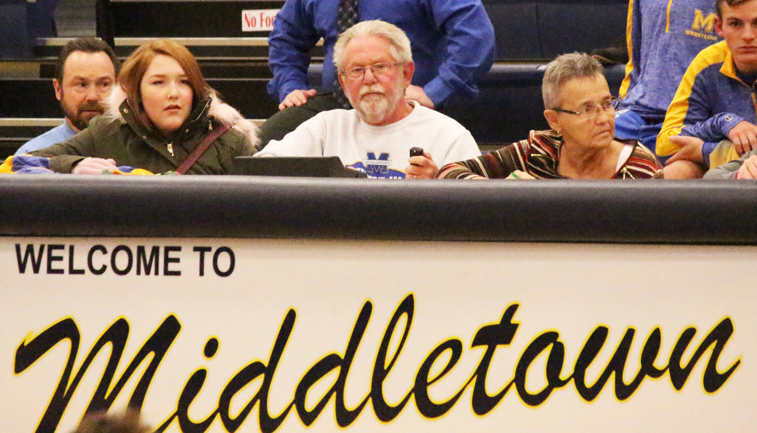 Earl Bright III, center, works the scoring table at a Middletown wrestling match in late December.