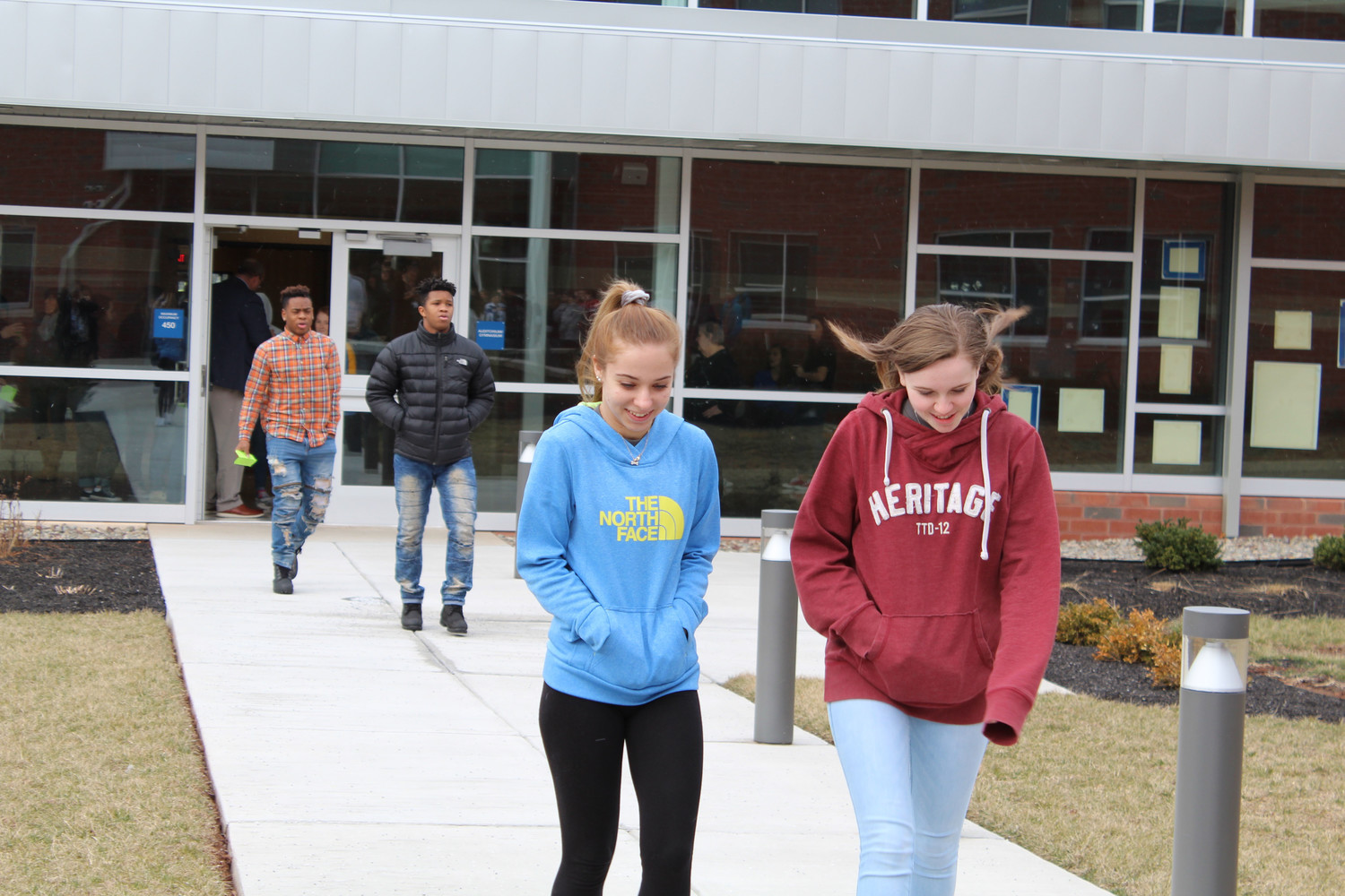 Juniors Abrielle Spagnolo and Alexis Harmon walk into the courtyard to participate in the walkout.
