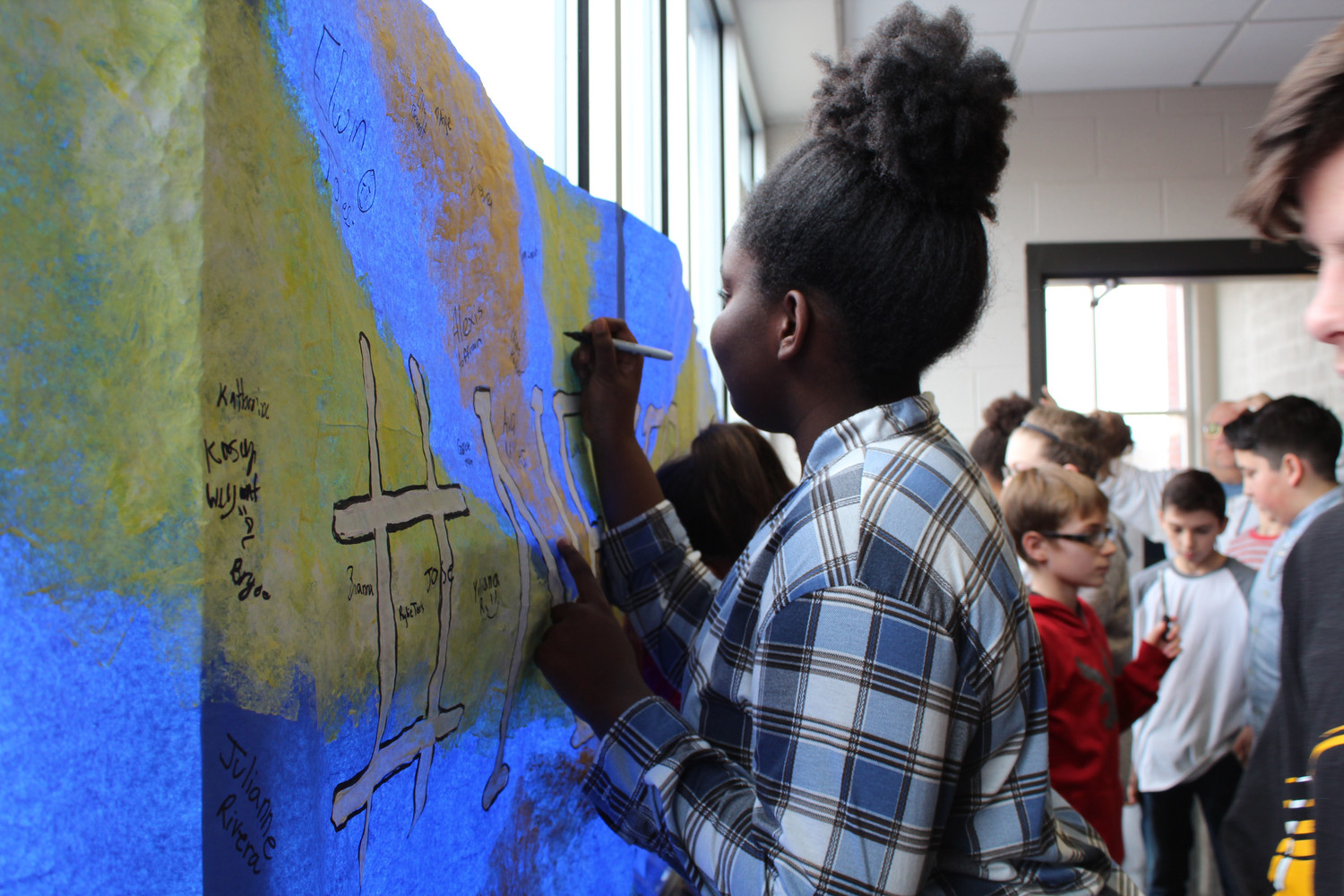 After the moment of silence, students like Sade Robinson signed a banner that will hang in the lobby.