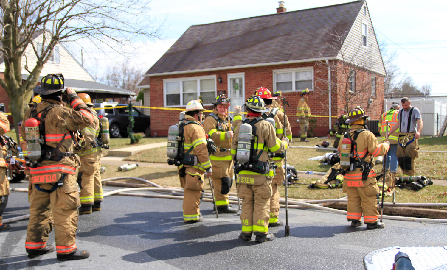 Firefighters regroup outside a house on East Roosevelt Street on Monday March 19.