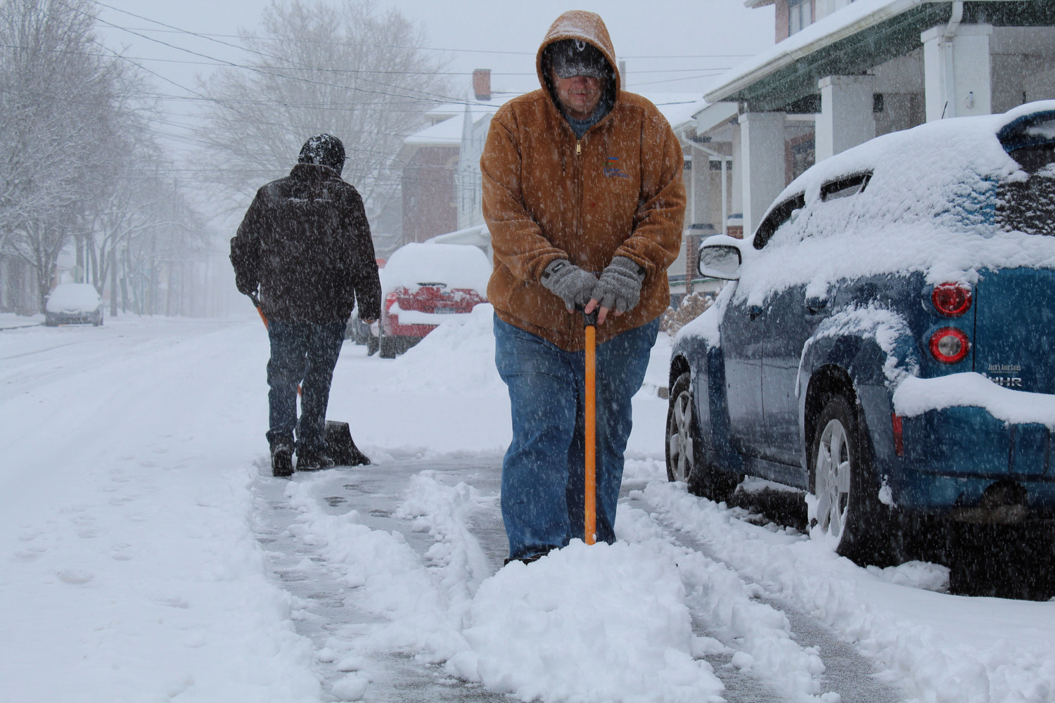 Randy Kennedy shovels snow out of the street.