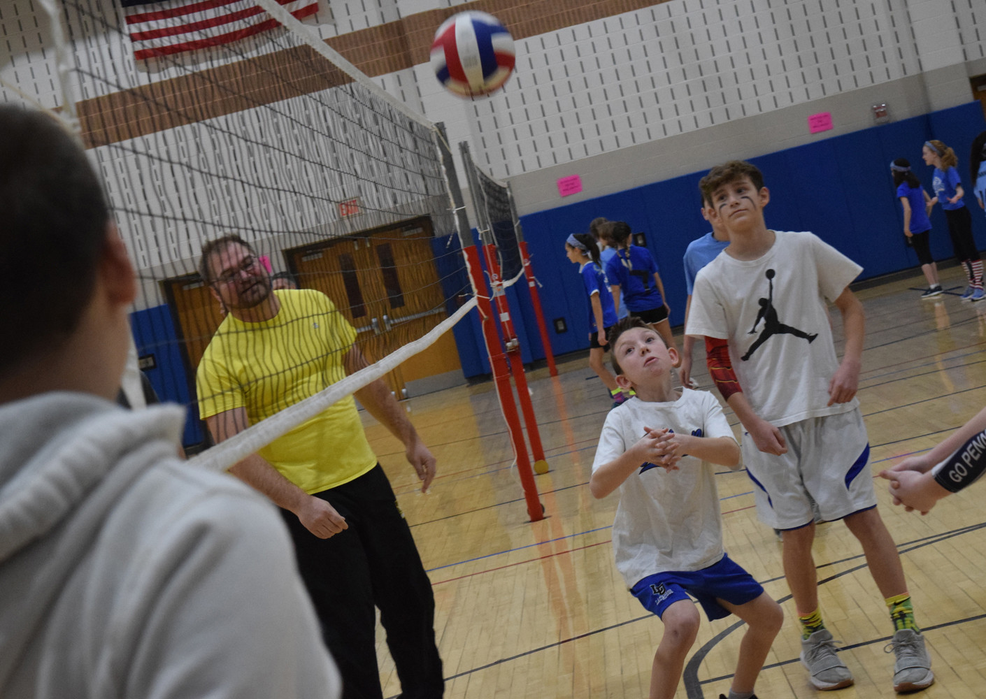 Ethan Kurtz goes for a save while his teammate Ty Weigher and school staff member Daniel Kauffman look on.
