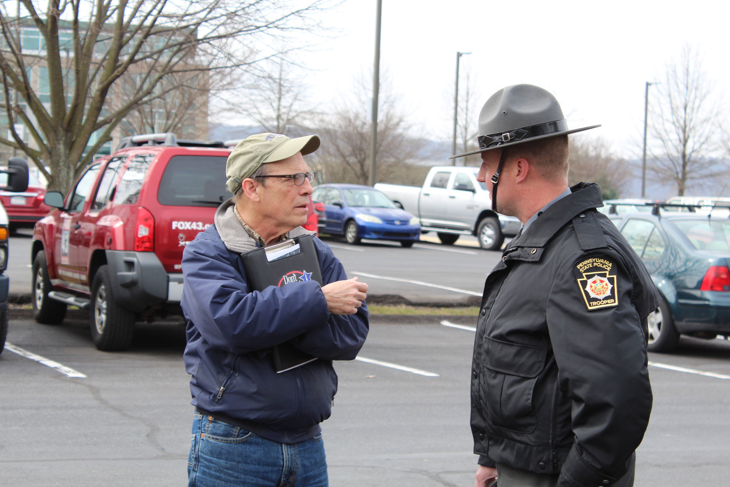 PennDOT's Greg Penny talks to State Trooper Brent Miller prior to a press conference on April 6.