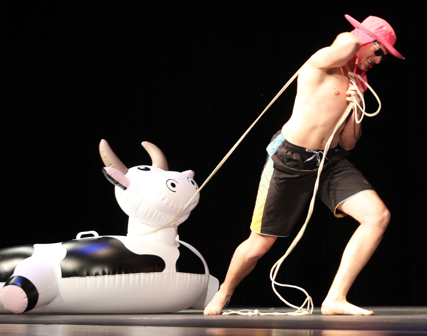 Matt Schopf hauls a cow floaty onto the stage during the swimsuit portion of the Mr. Middletown pageant on April 13.